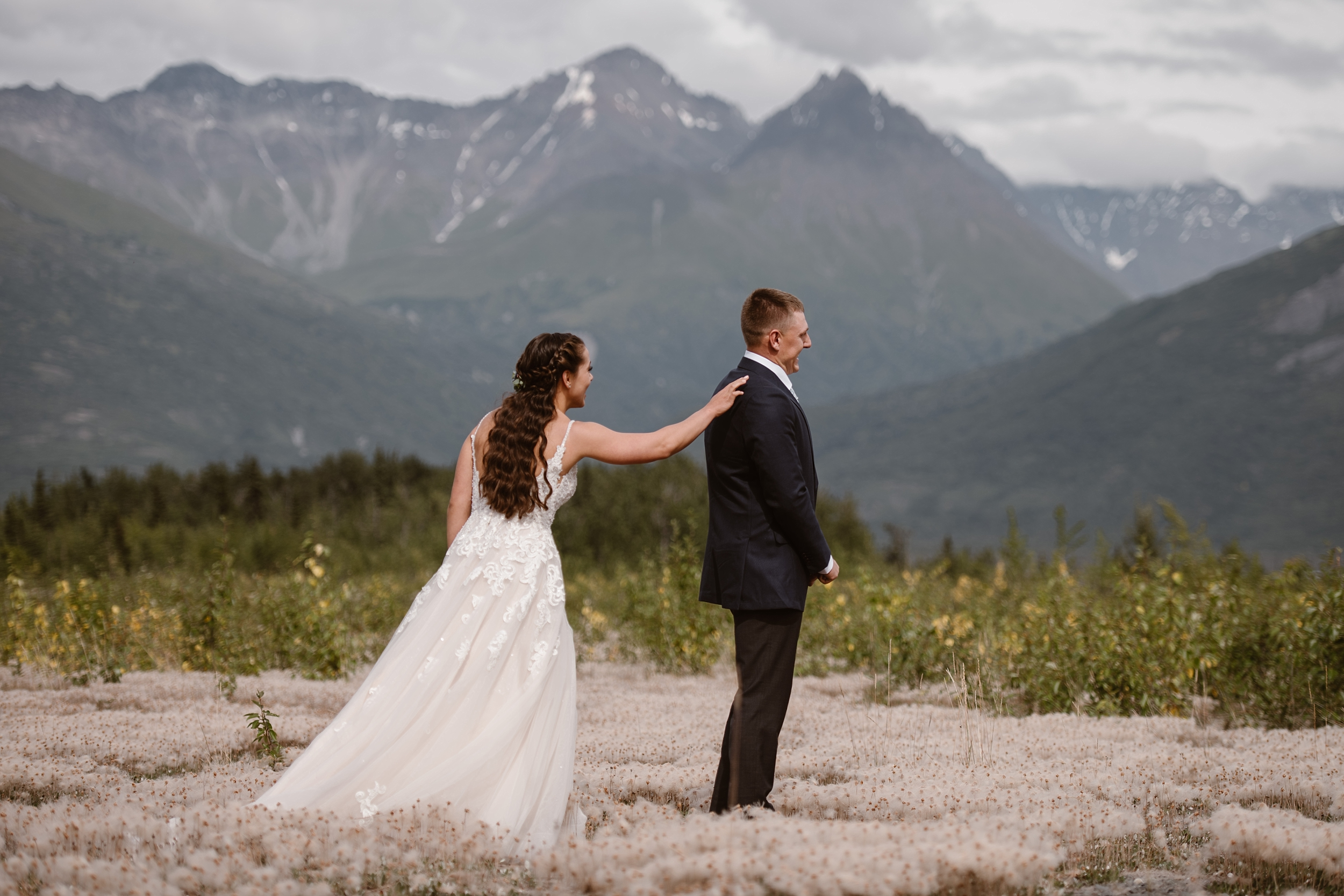 A first look is possible, even in Alaska destination elopement weddings. Jordyn reaches out toward Connor, who is looking away and waiting her go-ahead to see her in her wedding dress. The two stand among a field of flowers with dramatic Alaskan mountain peaks and lush foliage in the background.