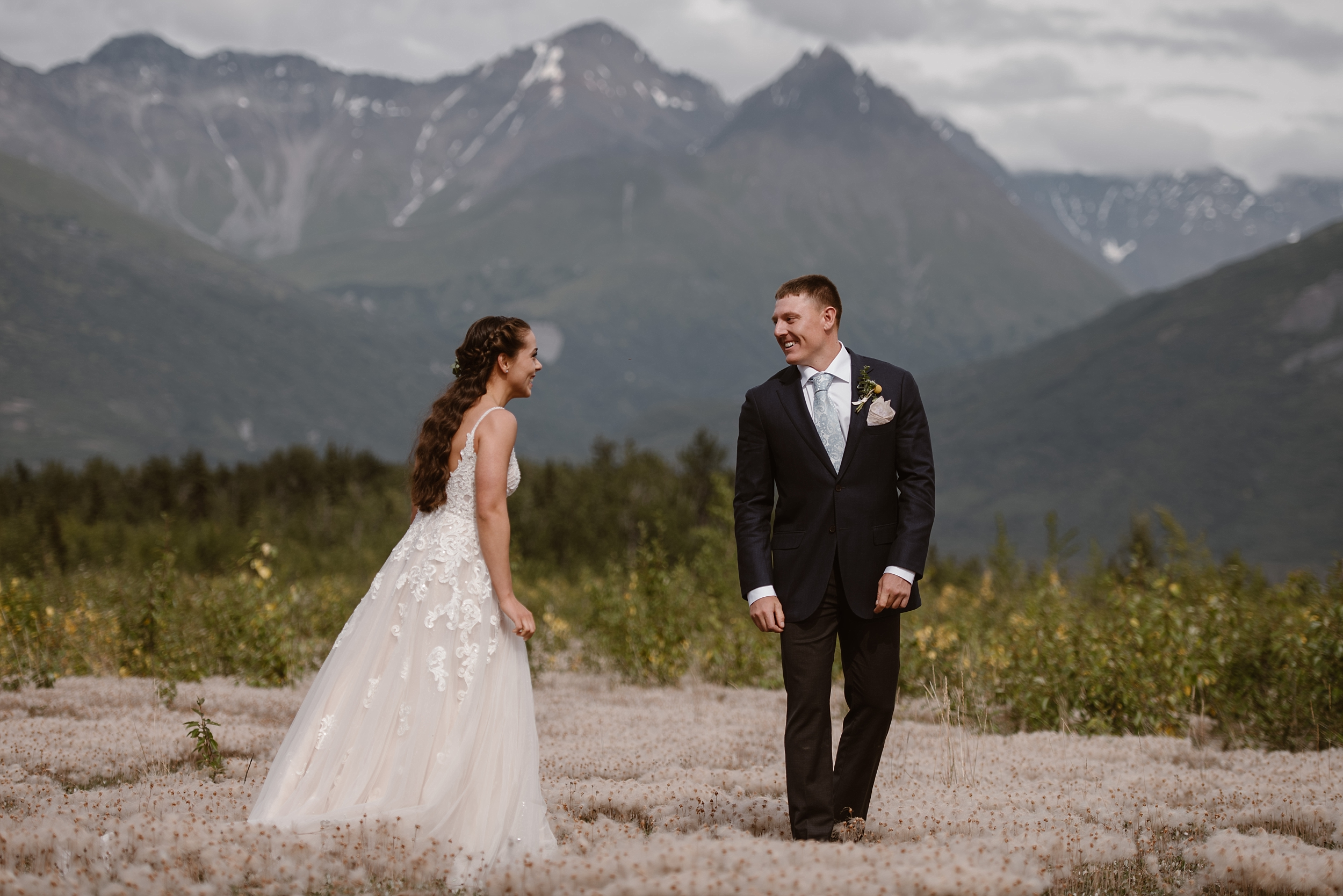 Jordyn and Connor have their first look in this elopement photo. The two of them stand in a field of beautiful flowers on the Knik River with mountains in the background. This photo was captured by Alaska elopement photographer Adventure Instead.