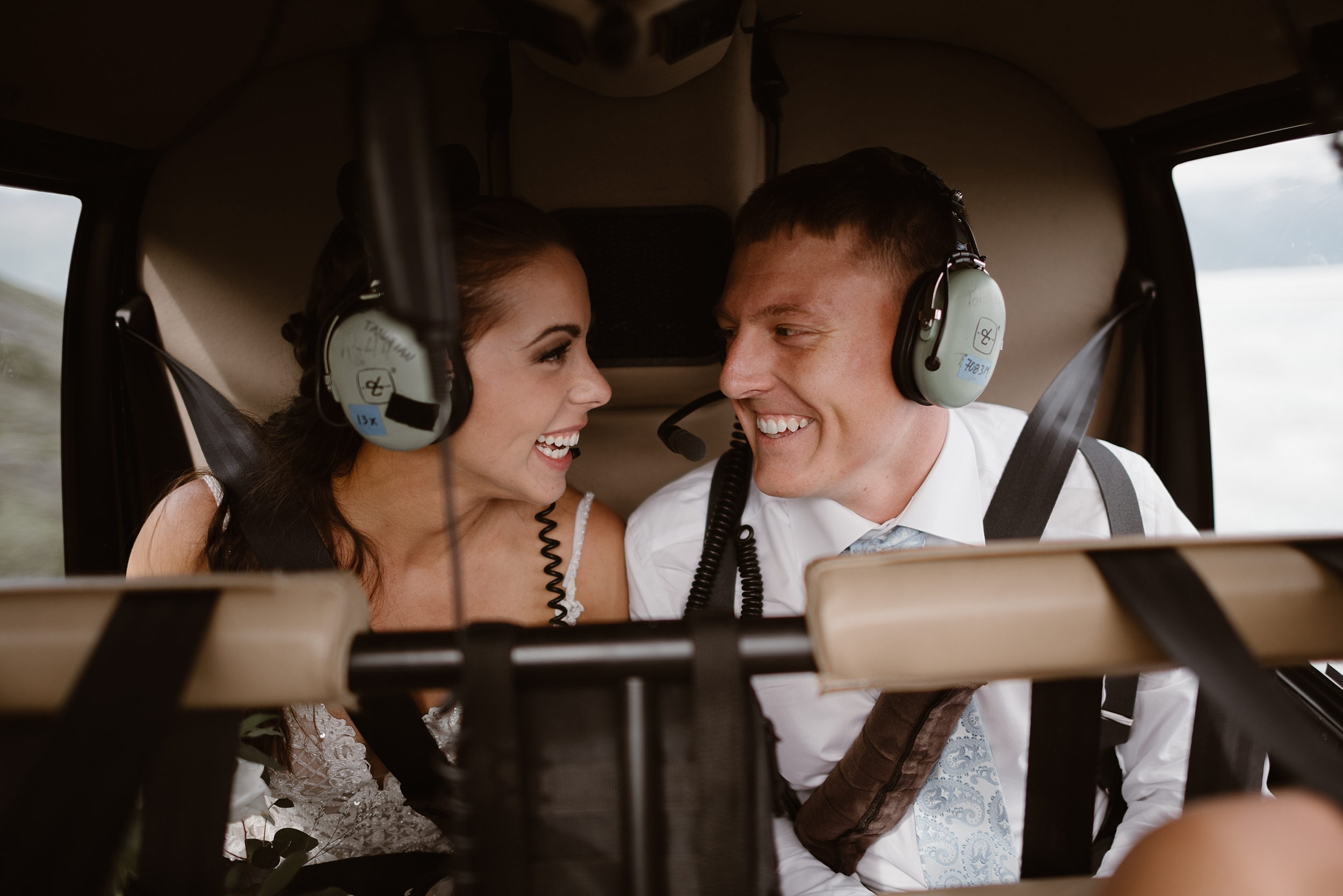 Both Jordyn and Connor sit inside the back of the helicopter as they prepare to take off for their Alaska helicopter elopement story. The stare at each other, smiling, with a stunning backdrop of Alaska green and blues in the windows.