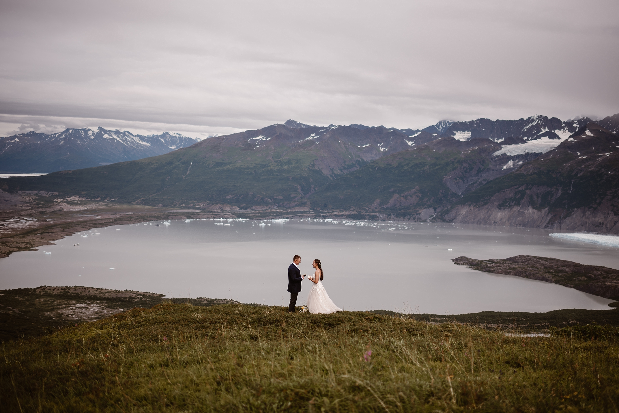 Jordyn and Connor stand in a grassy field above a glacial lake with snowy mountain peaks in the distance. The two read their vows to each other during their alaska destination wedding in this photo captured by Adventure Instead, an elopement photographer.