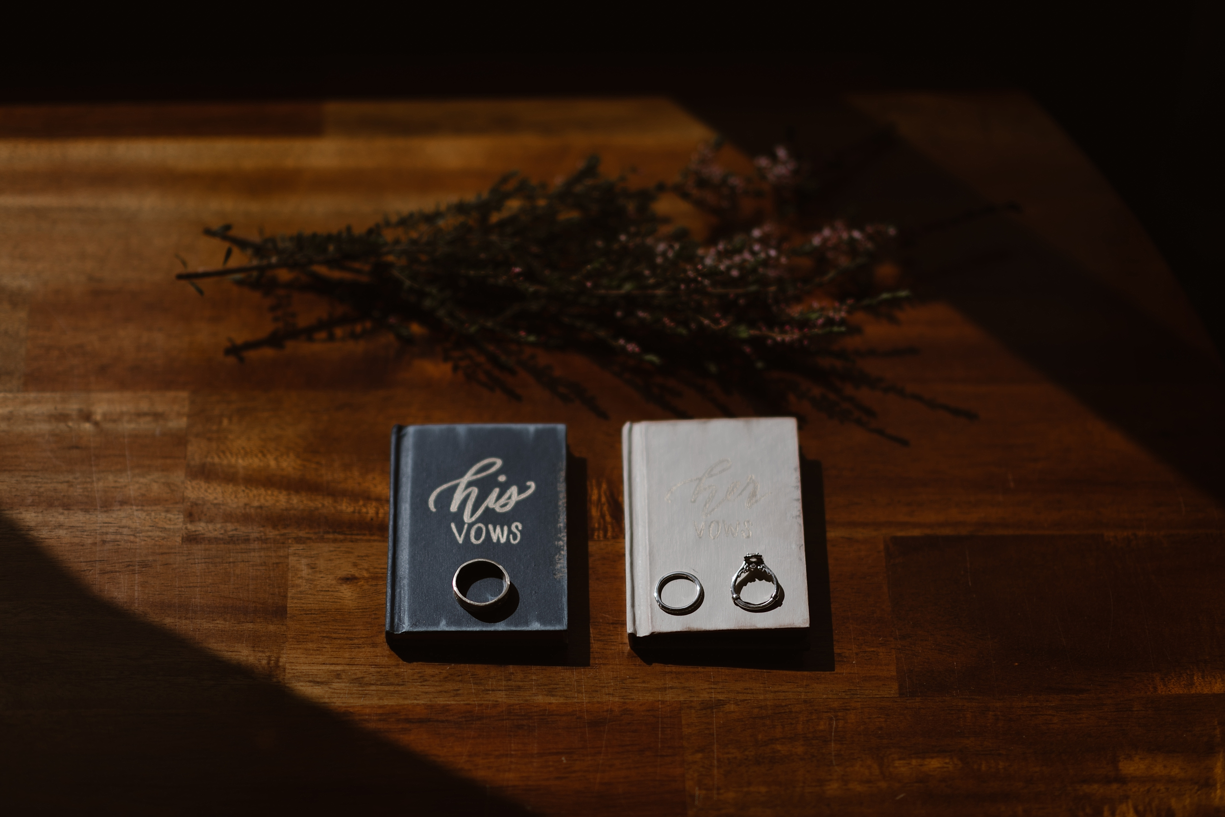 Laying on a wooded table in an Alaskan Airbnb are two books, one titled his vows and the other titled her vows. Above the vow books are dried flowers and laying on top of the books are wedding rings and the bride's engagement ring. All of these items will be included in the Alaska helicopter elopement story, captured by elopement photographer Adventure Instead.