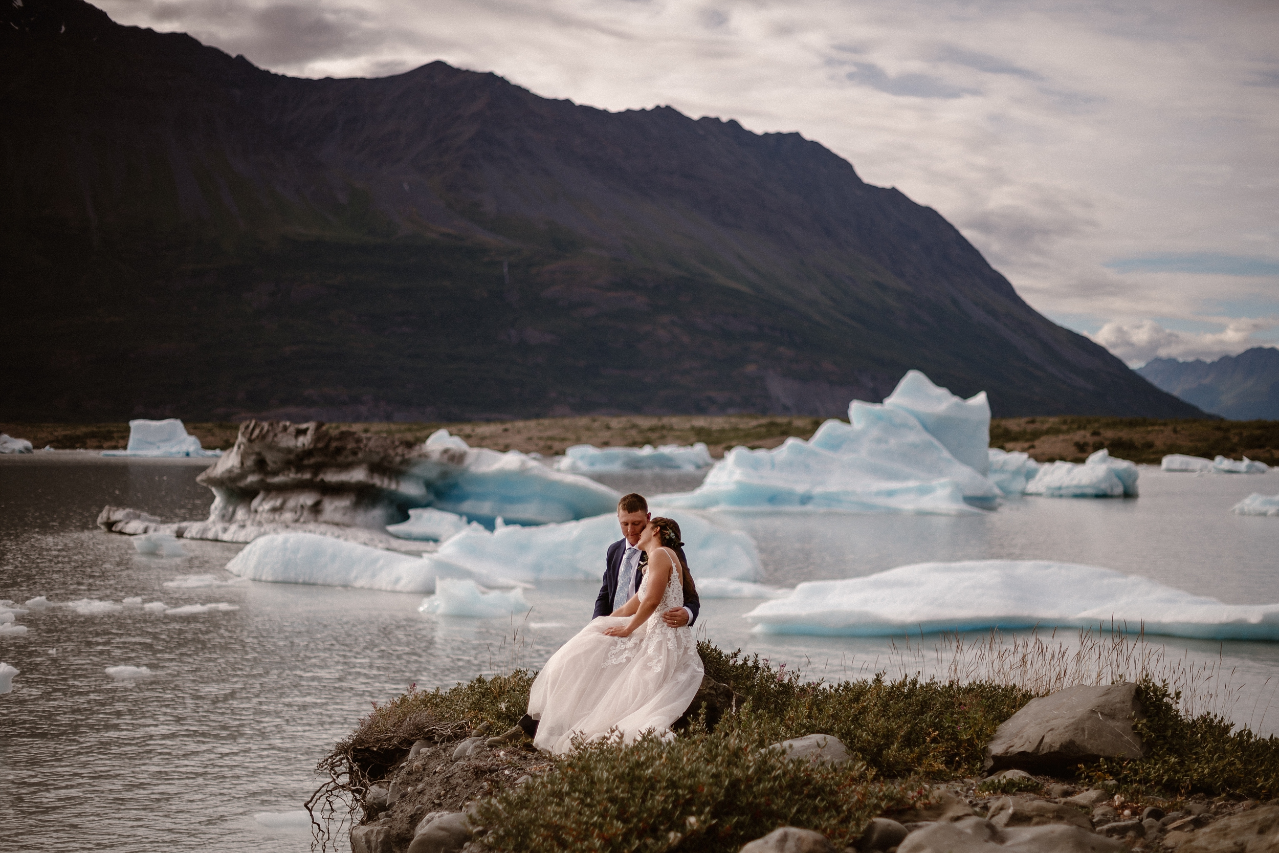 Sitting side-by-side on a rock next to a glacial lake, Jordyn leans her head down onto Connor's shoulder. In the background of this elopement photo captured by Adventure Instead, Alaska wedding photographers, are green and granite mountains and icy peaks.