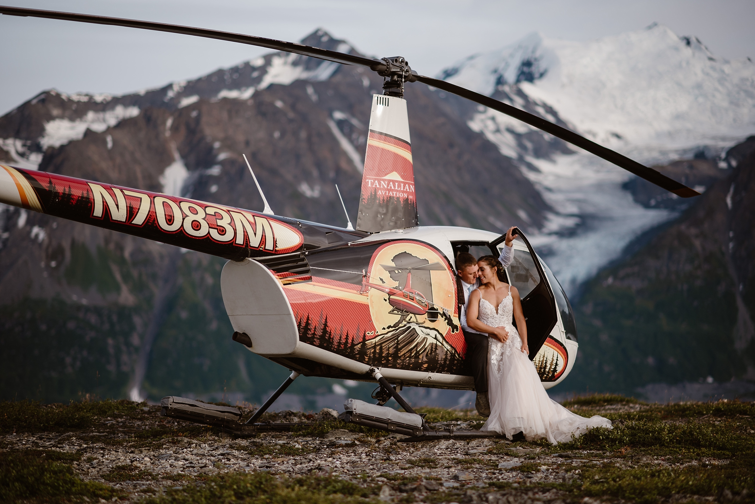 The bride and groom sit in the helicopter in front of an enormous, glacial-mountain-peak. Connor , the groom, sits with his legs outside of the open helicopter door while Jordyn, his bride, sits on his lap. The two nuzzle up close in this elopement photo captured by Adventure Instead, Alaska elopement photographers.