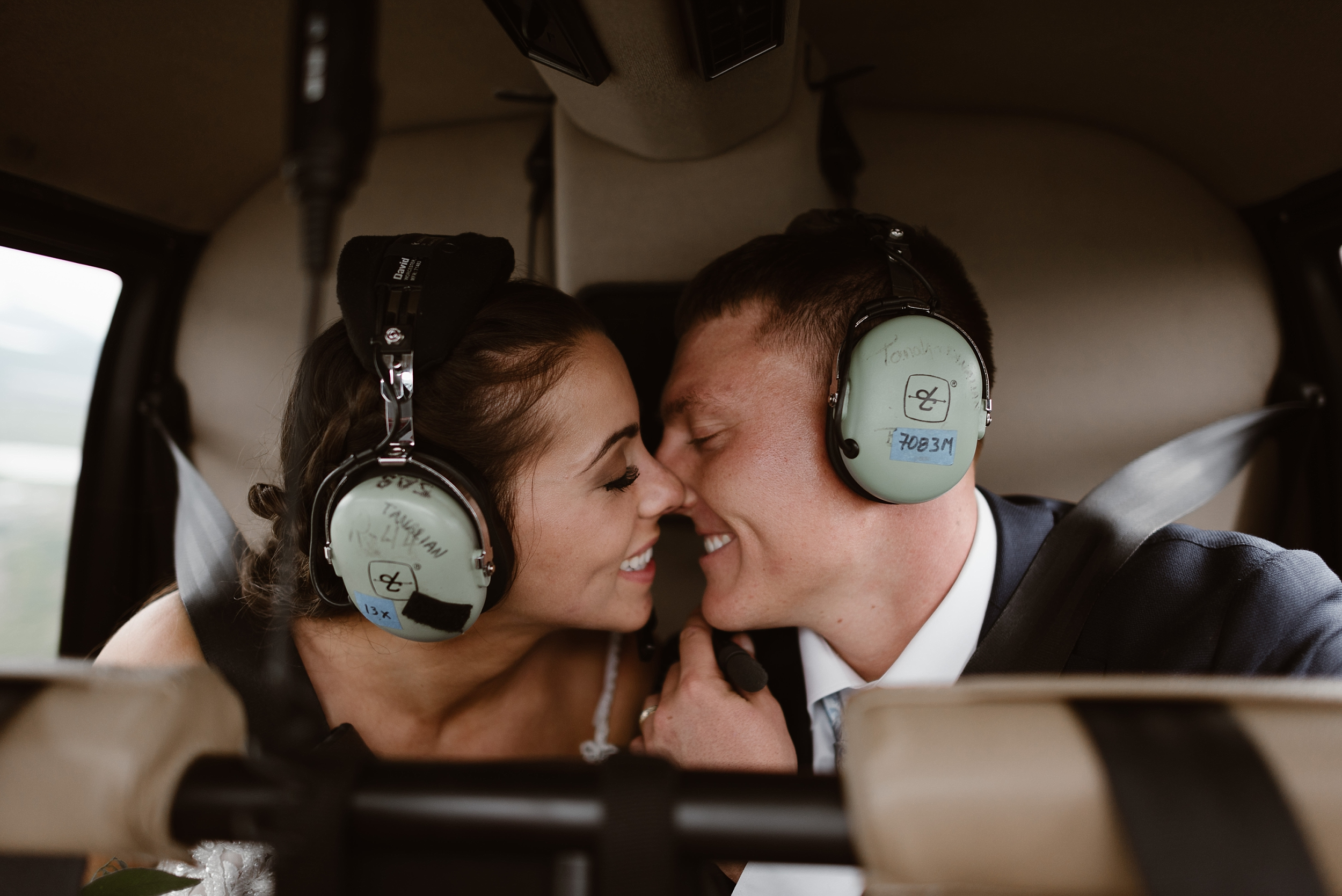 In the back of the helicopter, Jordyn and Connor, the bride and room, pull each other in close until they're almost kissing. With their eyes shut, they lean in as the helicopter flies them to their next destination during their helicopter elopement.