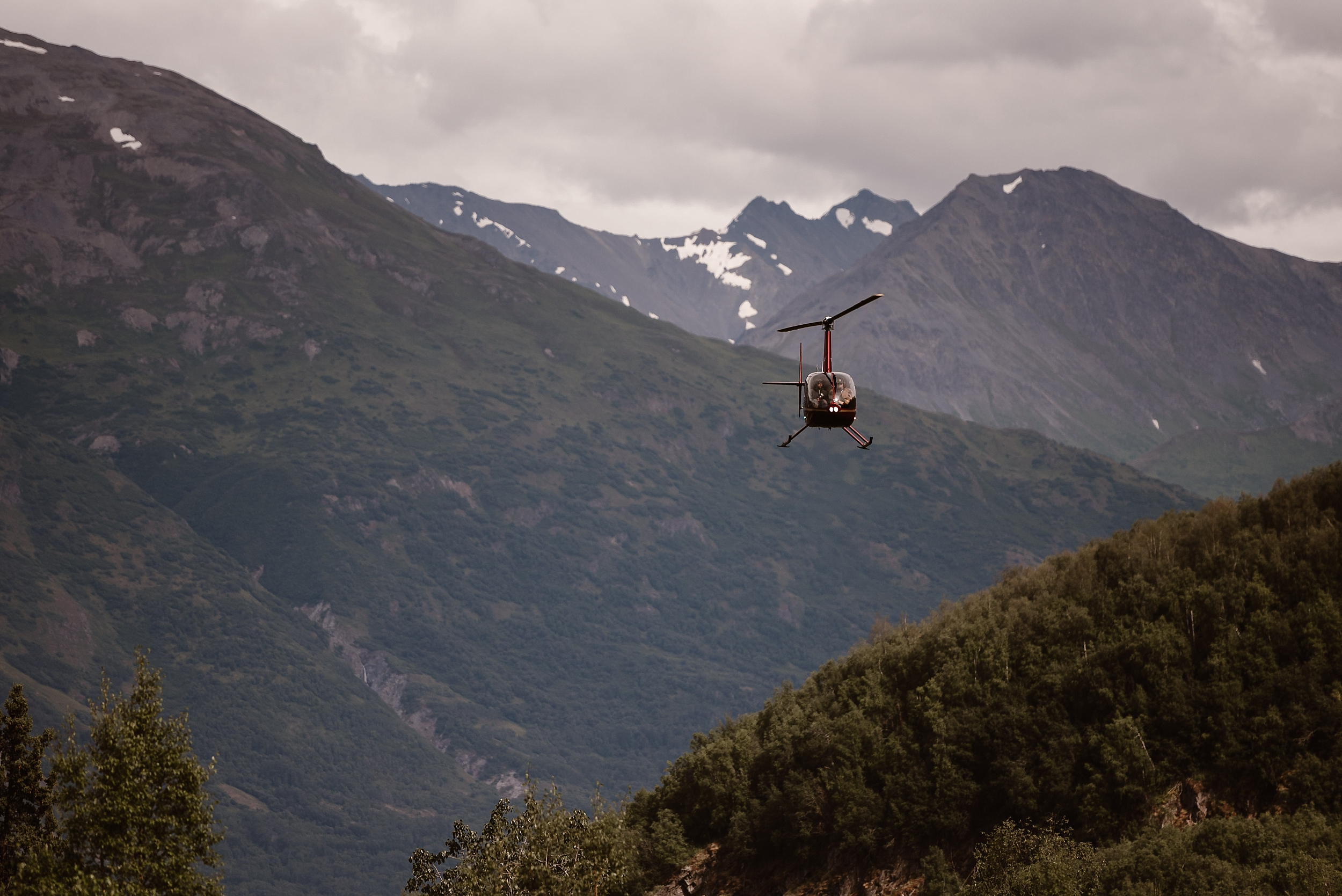 In the distance, among green hills and snowy mountain peaks, a helicopter flies toward the camera. This elopement photo, captured by Alaskan elopement photographers Adventure Instead, shows the helicopter that will chauffeur Jordyn and Connor on their helicopter elopement.