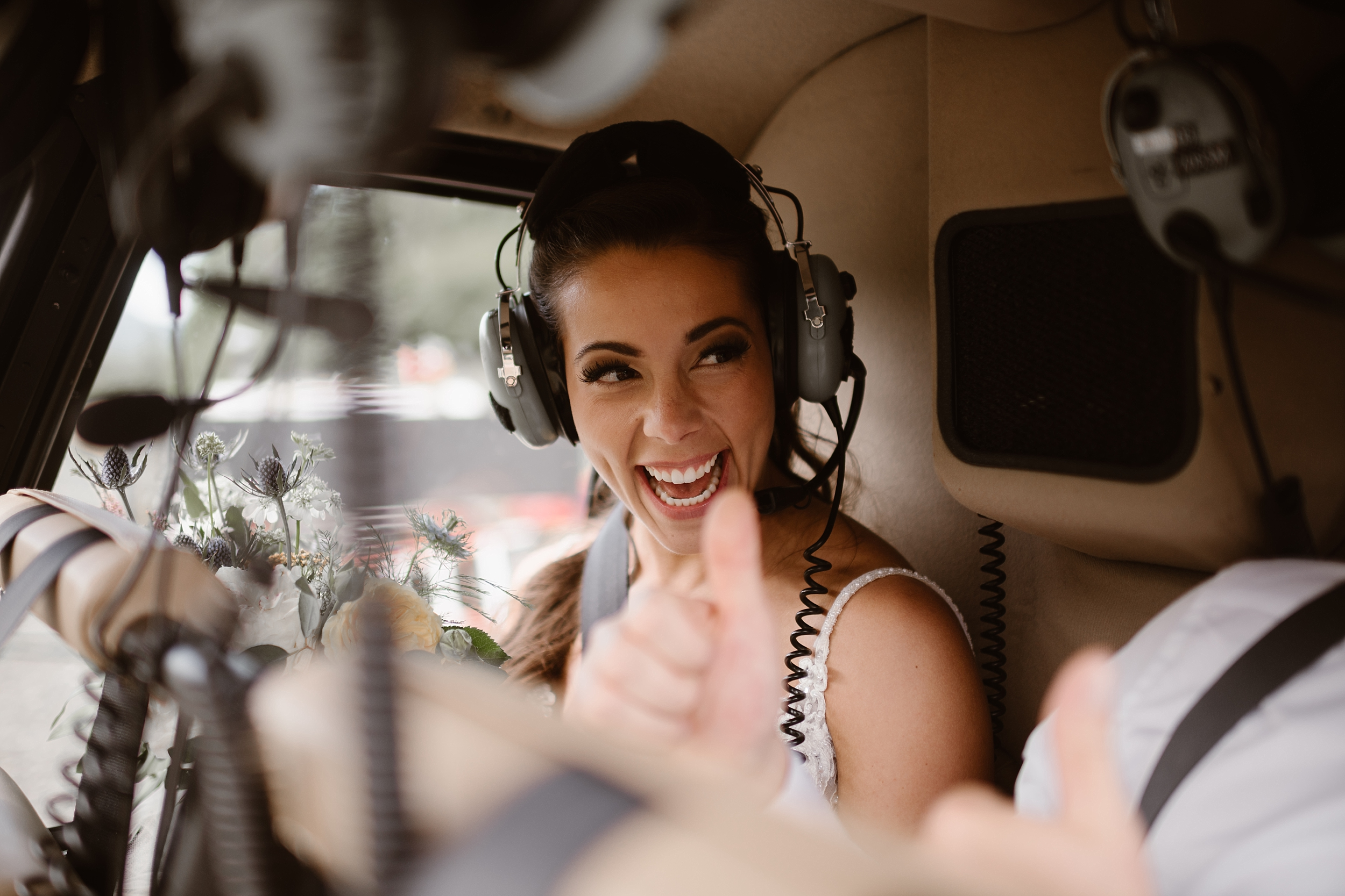 Jordyn smiles widely as she sits in the back of the helicopter. In the corner of the image, captured by elopement photographer Adventure Instead, Connor gives Jordyn a thumbs-up as they take off to their next destination on their helicopter elopement.