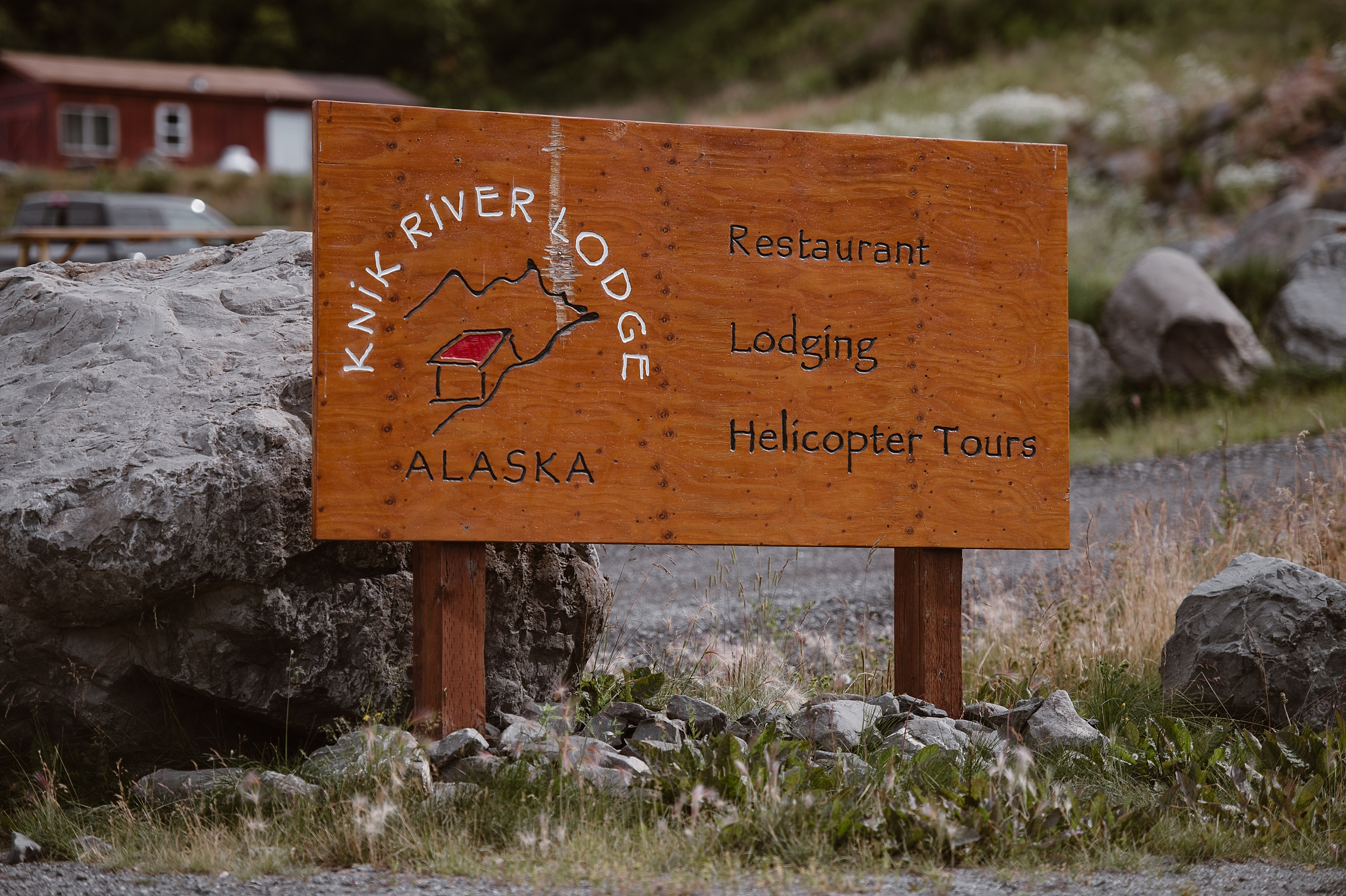 In this image, a wood sign is in focus displaying the Knik River Lodge in Alaska, a restaurant, lodge, and place for helicopter tours. This is where Jordyn and Connor chose to do their first look, sign their marriage license, and who they chose to take a helicopter tour with for their Alaska elopement. This photo was captured by Alaska wedding photographer Adventure Instead.