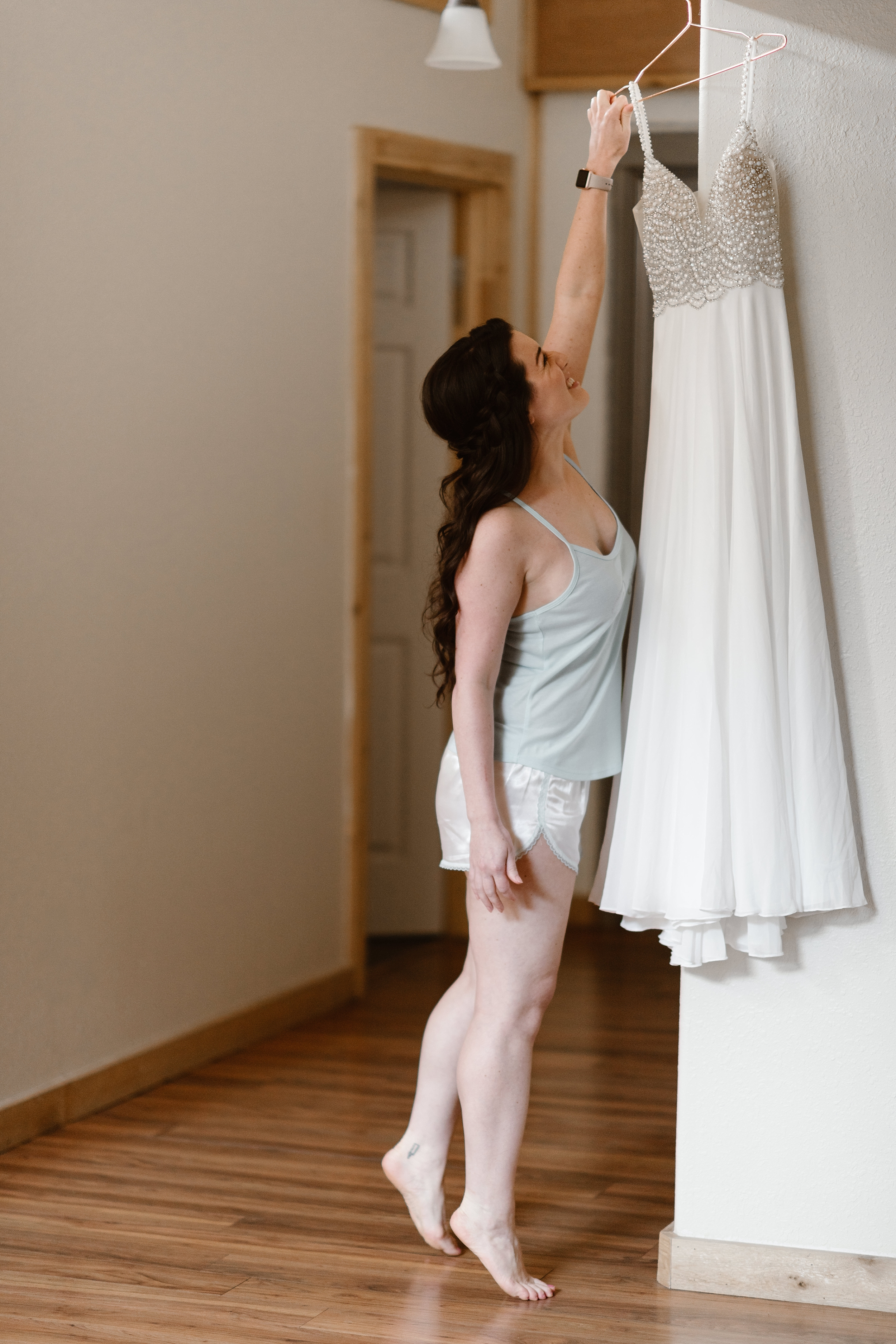 The bride, Katie, reaches up to grab her white wedding dress that's hanging on a pink hanger off of a wooden rafter in her Colorado Airbnb. Katie, in satin shorts and a light blue tank top has her hair styled and her makeup on, and as she reaches up on her tiptoes to get her dress down for her elopement ceremony, she sports a huge grin on her face.