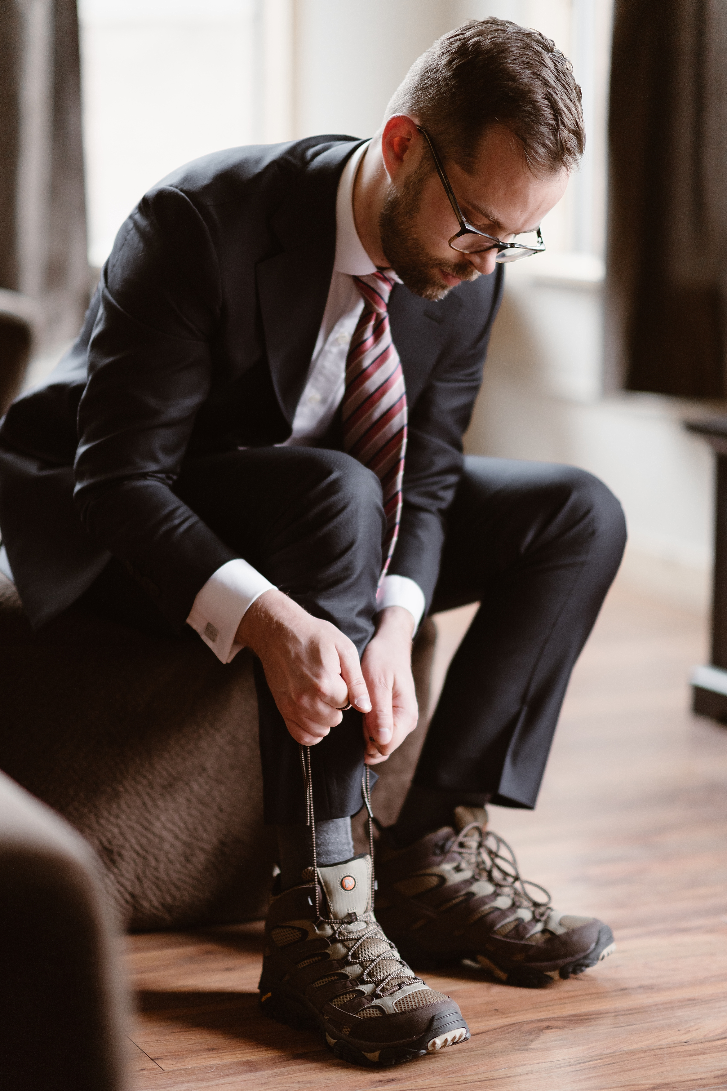 Logan, the groom laces up his hiking boots in his Ouray, Colorado Airbnb as he prepares for his Colorado mountain wedding to his bride, Katie. He sits on a brown leather stool as he pulls the laces up tight to ties his boots, revealing a grey sock underneath.