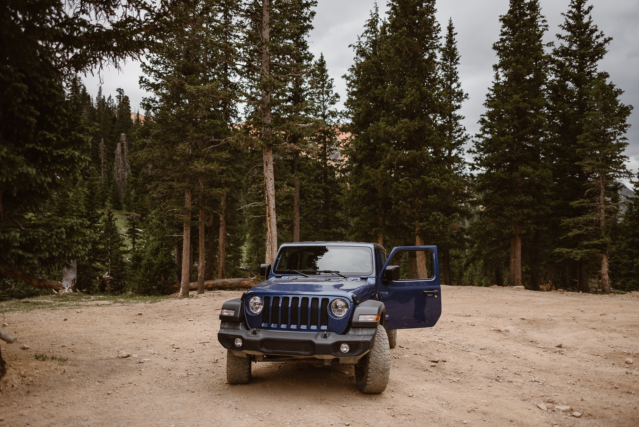 A navy blue Jeep stands parked on a dusty, Ouray, Colorado mountain road surrounded by tall, evergreen trees. This 4x4 off-road vehicle is Katie and Logan's Jeep wedding car, which will take them off-road for their Colorado mountain wedding — one of the best elopement ideas.