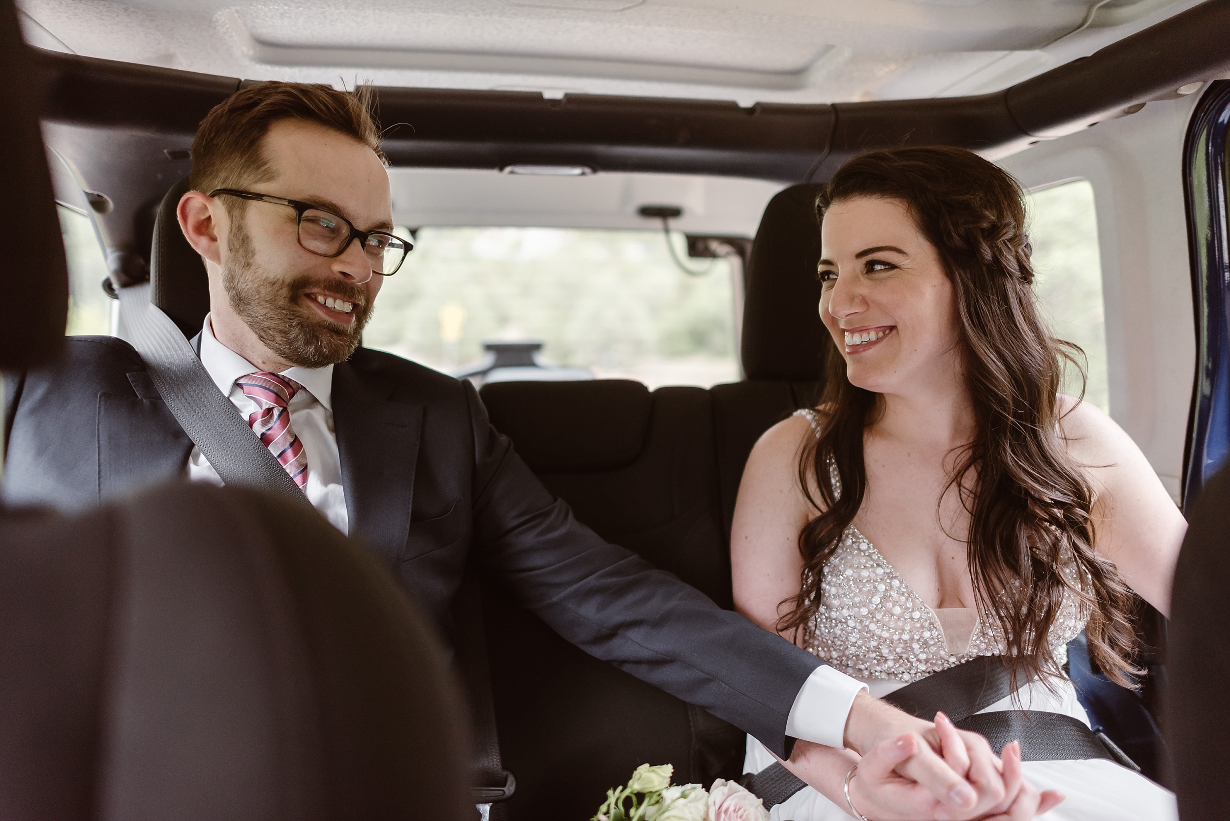 The bride and the groom buckle up in the backseat of the jeep. As Katie and Logan stare at each other, dressed in their wedding attire and prepared to start their 4x4 wedding, they grab hands and smile.