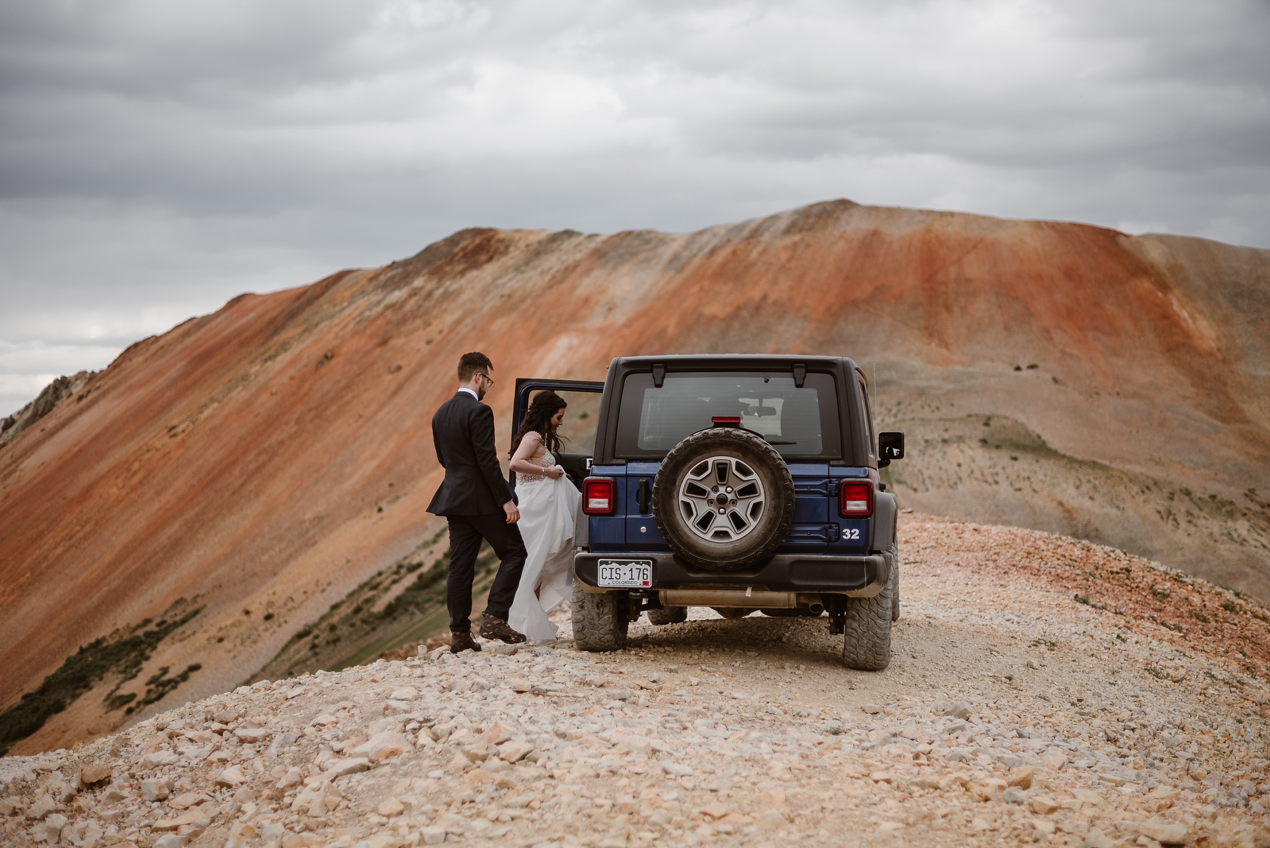 Katie and Logan, the bride and groom, climb into the adventure Jeep from where it's parked, on a dusty, rocky 4x4 road at the top of a mountain. The Jeep wedding car will take them to the next location where they plan to have their elopement ceremony for their Colorado mountain wedding.
