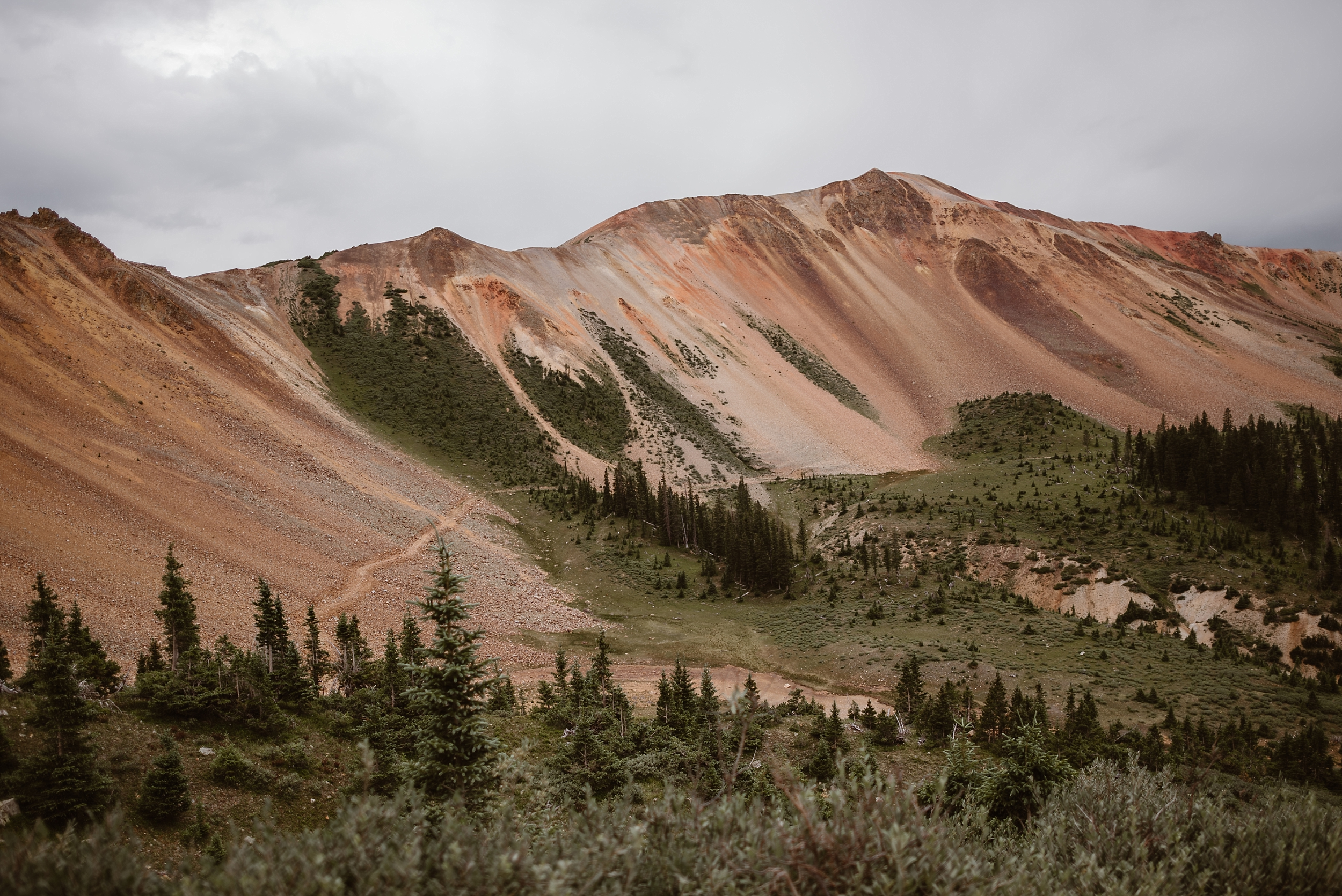 In this adventure photography shot, the reddish mountains of Ouray, Colorado juxtapose against the lush, green meadows at the base of them. Along the bottom of the mountain, an off-road 4x4 path is seen.