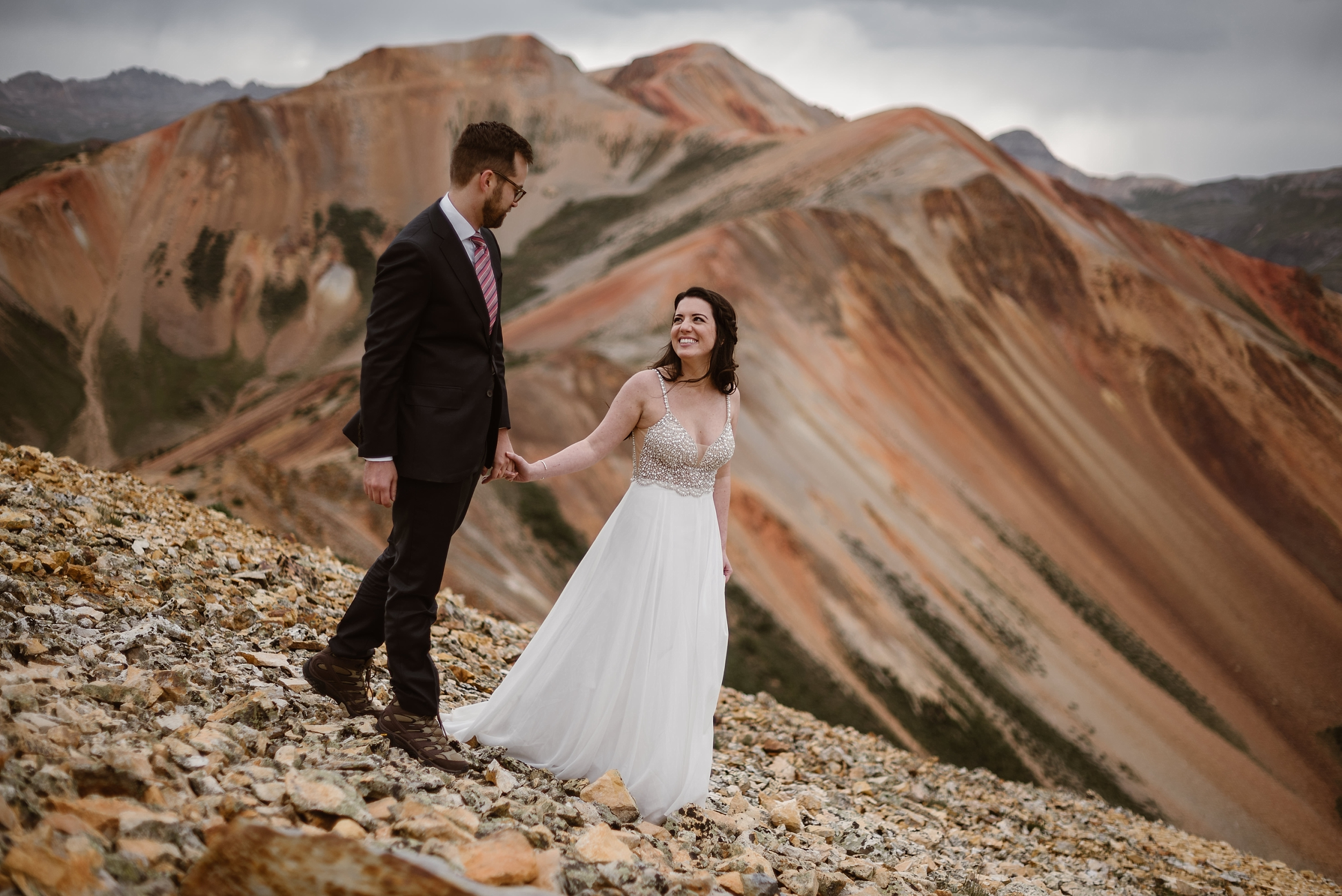The bride and groom Katie and Logan, hold hands as they make their way along the rocky mountainside in Ouray, Colorado. The two hike in their wedding attire, which is one of the most unique eloping ideas. They look at each other smiling among a gorgeous red mountain landscape in these elopement photos captured by Adventure Instead.