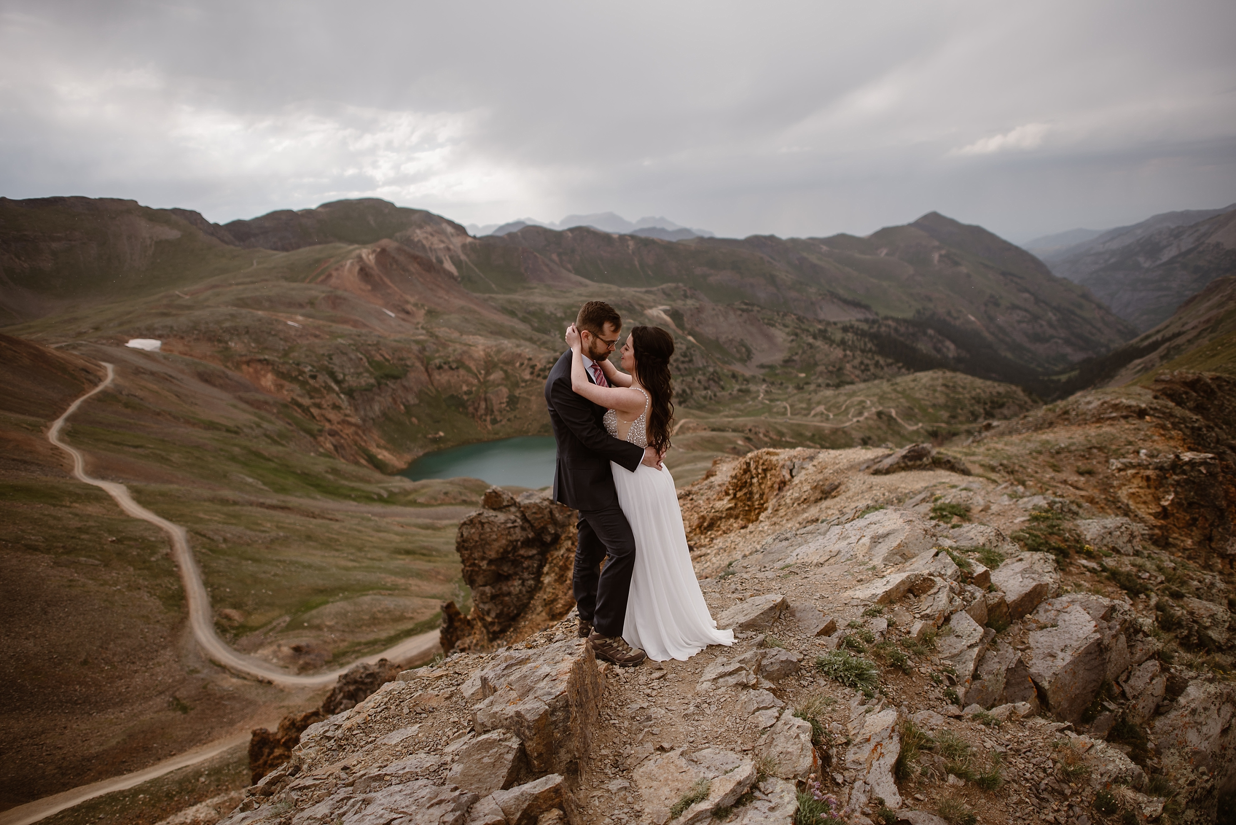 Katie and Logan stand on a rocky ledge at the very top of a gorgeous mountain. They embrace and hold each other close before their elopement wedding. Below them at the bottom of the mountain basin is a turquoise alpine lake and off to the left is an off road driving trail where their adventure Jeep drove.