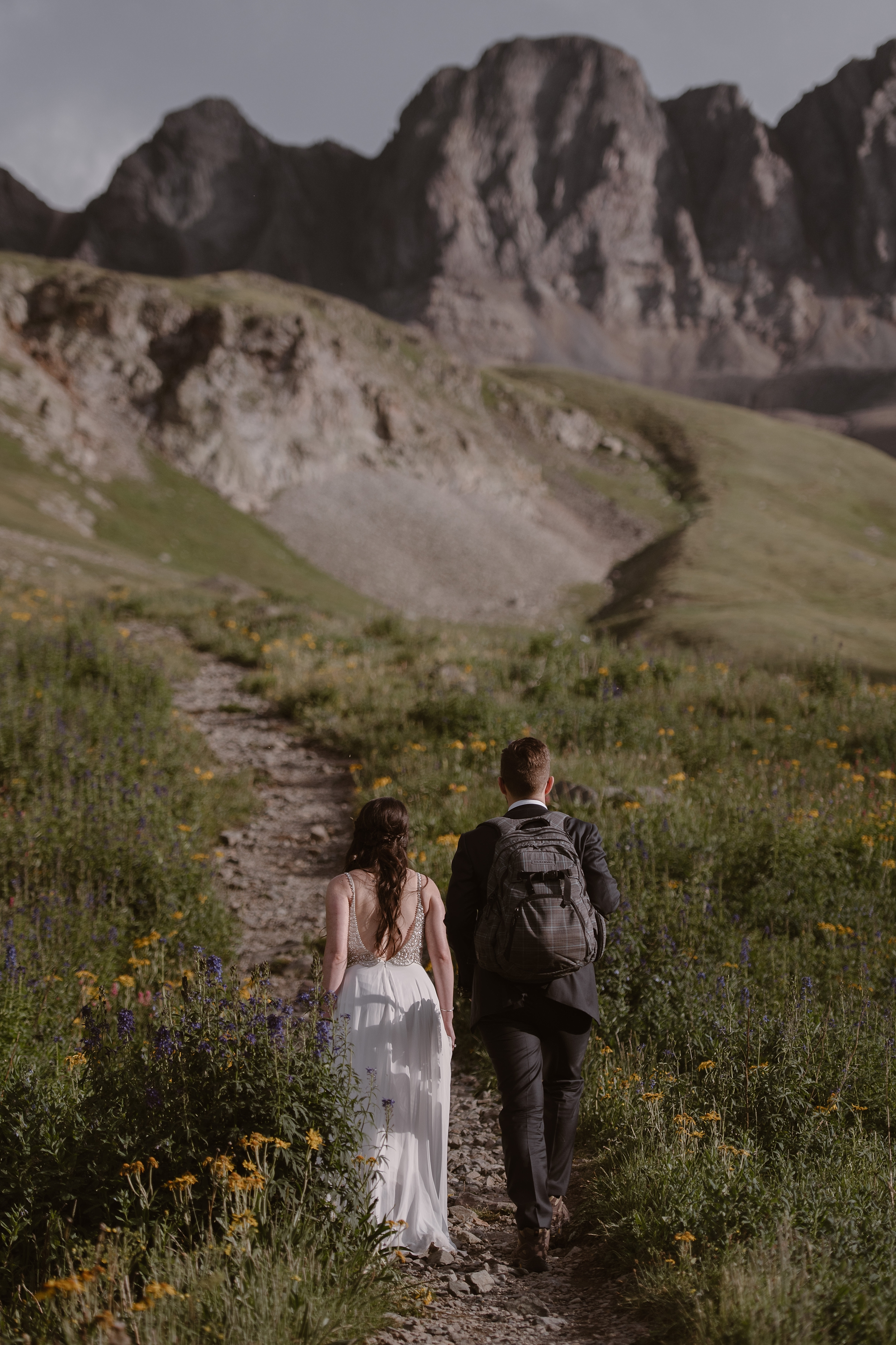 With the storm clear, Katie and Logan (the bride and room) take hands and walk up the trail toward the top of the mountain. Logan, carrying a backpack over his suit, takes Katie's hand as they walk between a bloom of mountain wildflowers in these elopement pictures captured by Adventure Instead, an elopement wedding photographer.