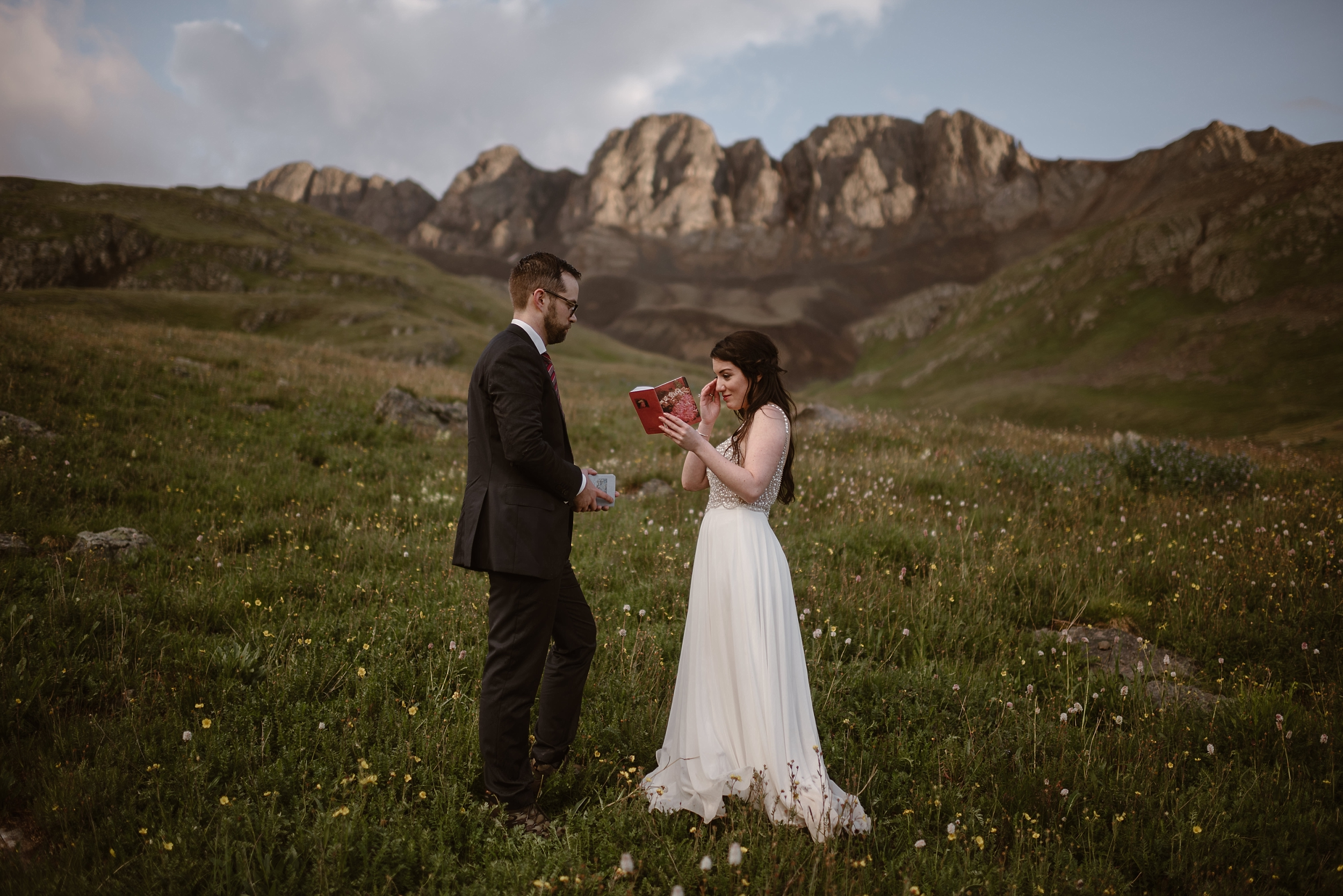 Katie, the bride, reaches up to wipe a tear from her eye as she reads her vows to Logan, the groom. The two stand in a meadow at a mountain basin in Ouray, Colorado. Wildflowers are in bloom and the sandy-colored mountains loom in the background. Katie and Logan chose this location for their destination elopement because it required off road driving to get there.