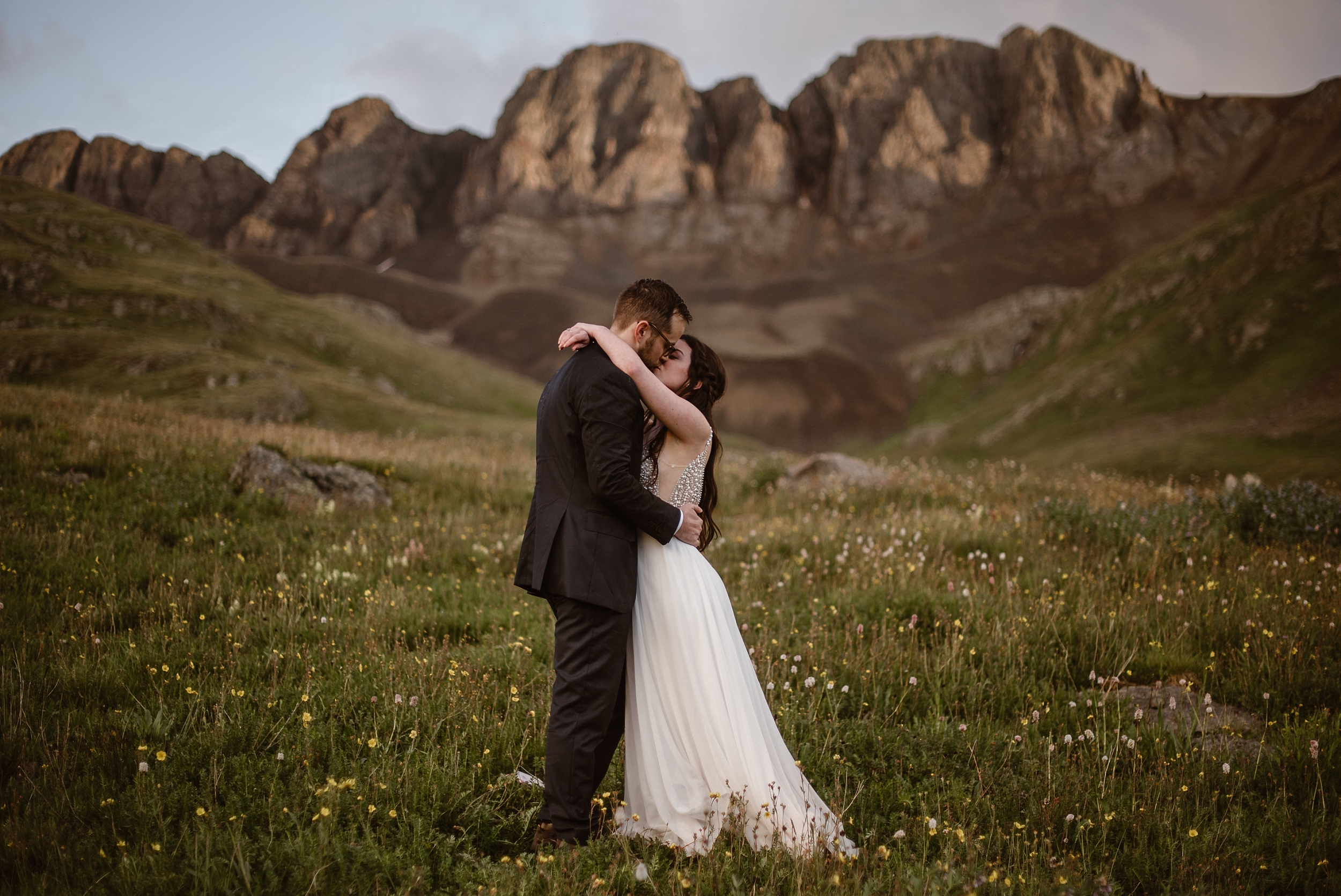 Katie and Logan embrace and kiss in a meadow in a mountain basin in Colorado. Wildflowers bloom all around them and sandy-colored mountains loom in the background. These elopement photos, captured by adventure photography company Adventure Instead, were one of the best elopement ideas that Katie and Logan had in mind for their 4x4 wedding on a Colorado mountain.