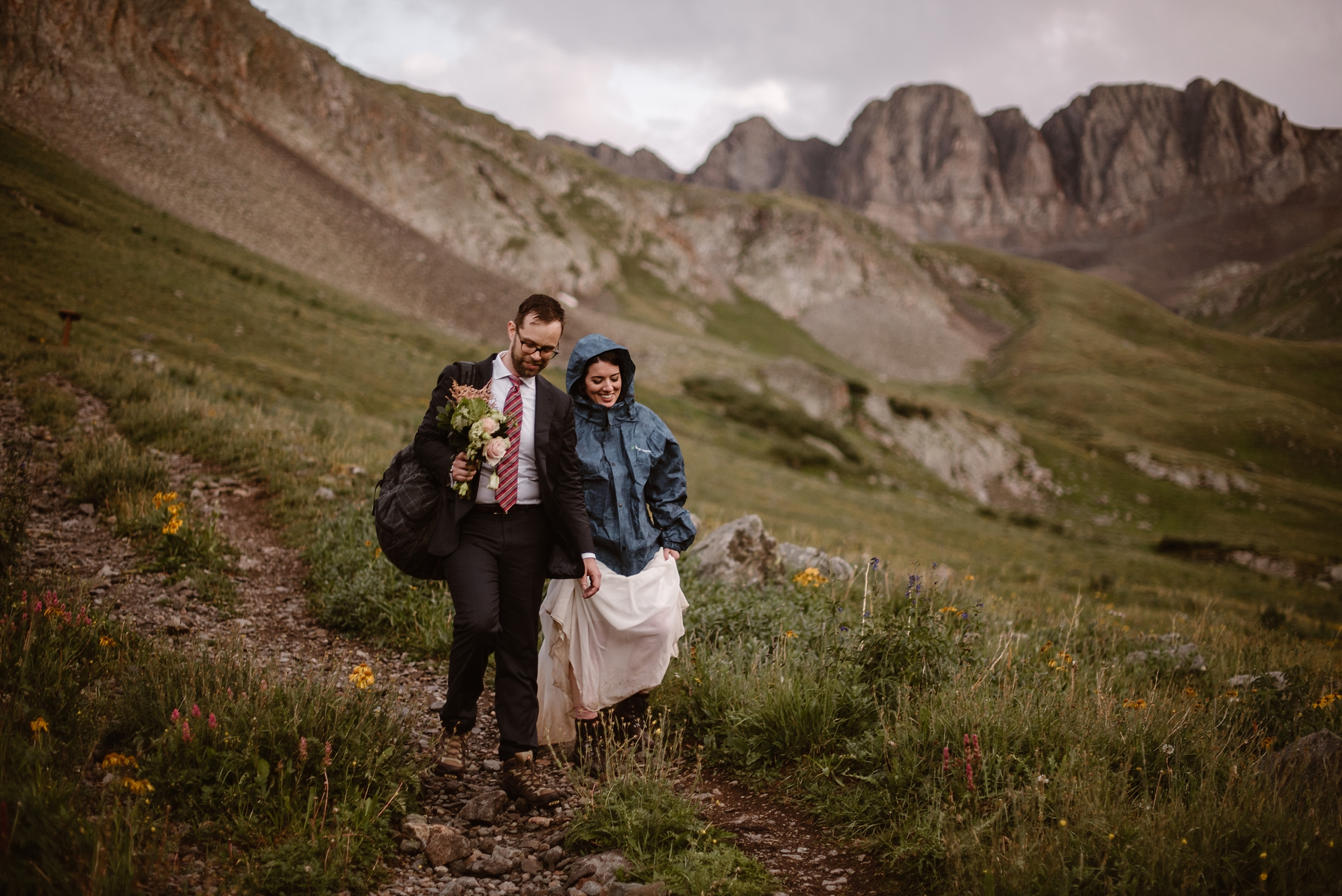 Katie and Logan, the bride and groom, head back down the mountain — a little muddier and dirtier than they started the day, but with big smiles on their faces. Katie's wearing a blue windbreaker and Logan walks beside her holding a bouquet of flowers and a hiking backpack.