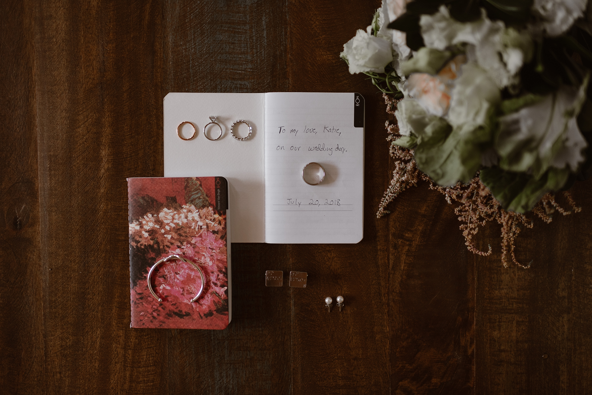 """On a wooded table, a vow book sits open with the words """"to my love, Katie, on our wedding day. July 20, 2018."""" On the open pages of the book sit four rings. On the table below the book, pearl earrings and engraved cuff links rest while they await their prat in the elopement ceremony."""