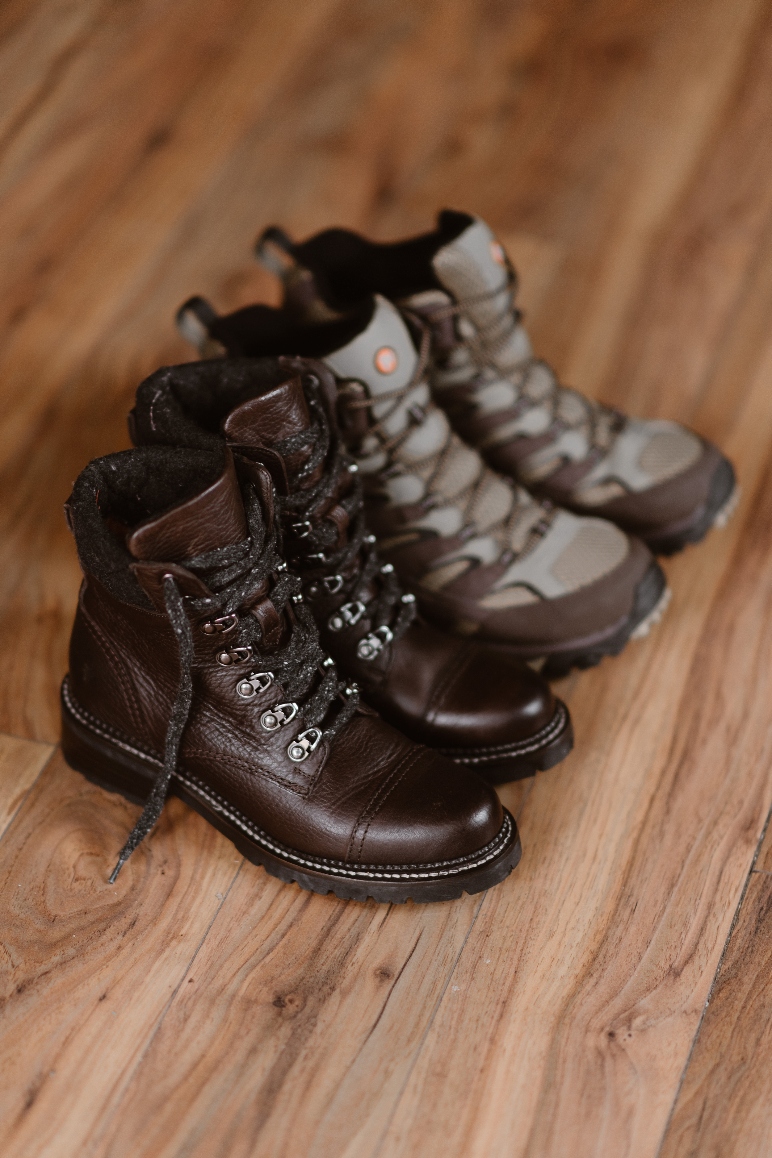 A dark pair of hiking boots and a lighter pair of hiking boots sit on a wooden floor in an Ouray, Colorado Airbnb. The boots, his and hers, belong to the bride and groom and will be a part of their elopement ceremony in their 4x4 wedding.