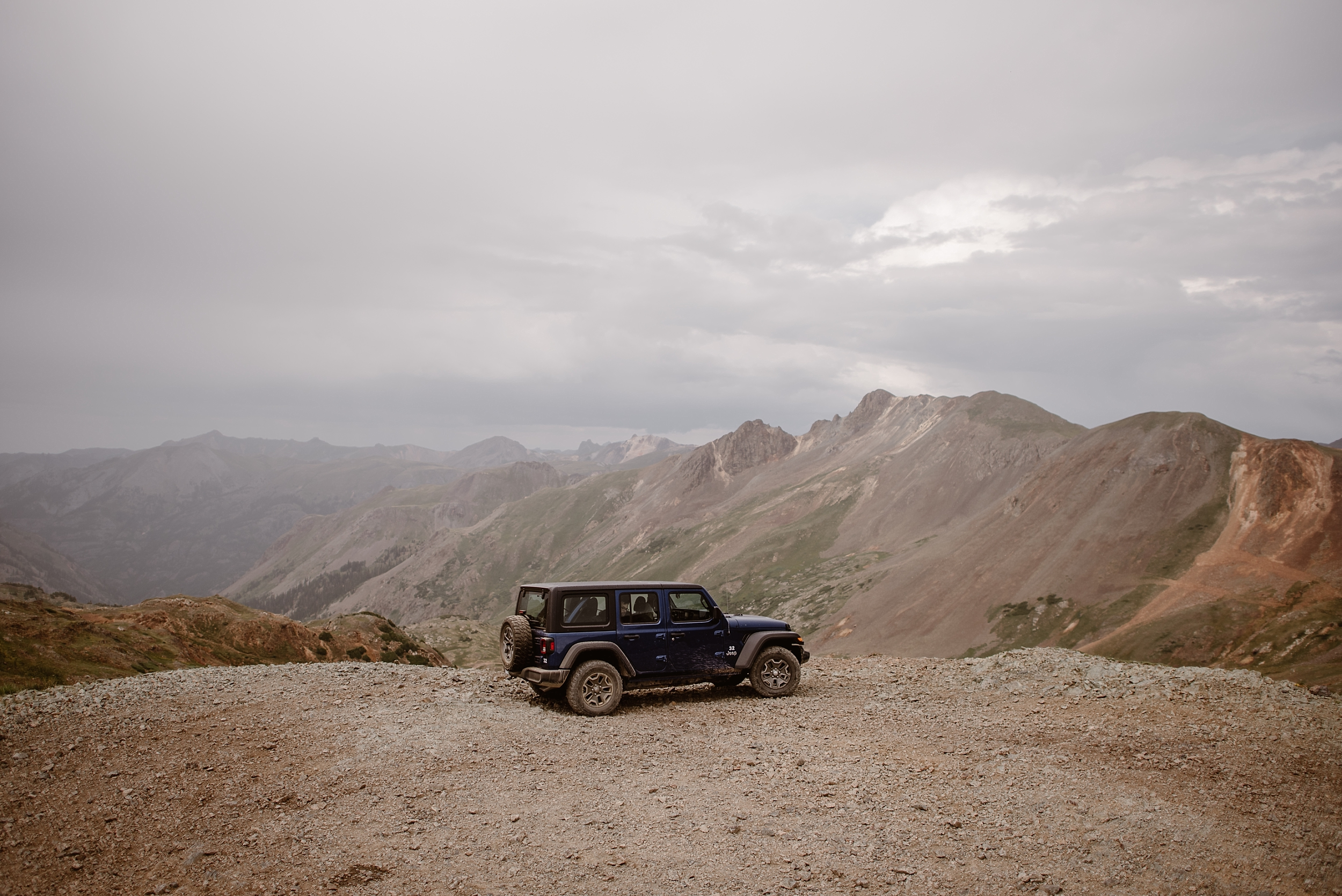 A navy blue adventure Jeep parks at the edge of a rock, sandy mountain. In the distance, a reddish mountain range can be seen. This was part of Katie and Logan's adventure elopement, and was one of the best elopement ideas yet.