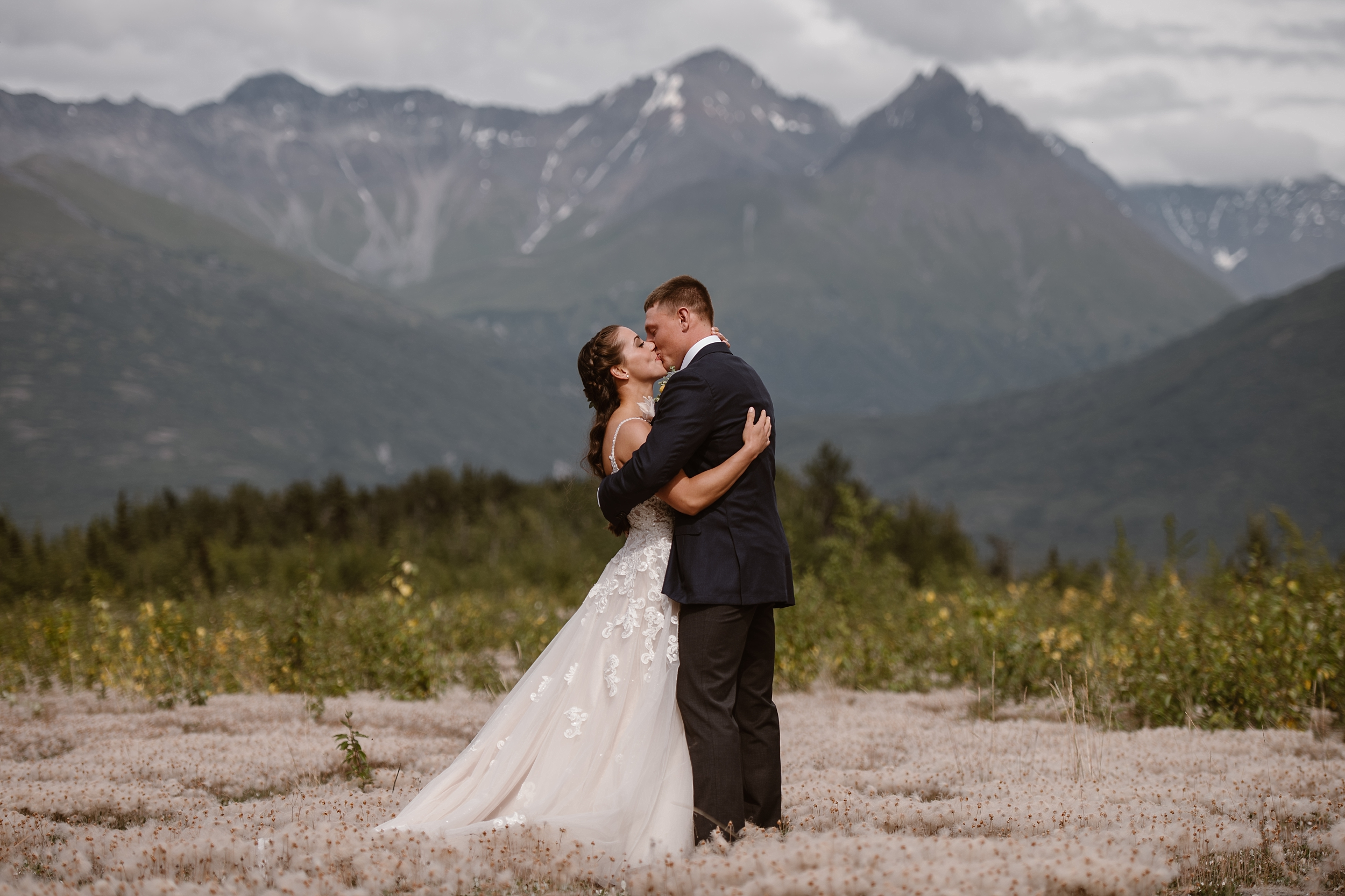 Jordyn and Connor embrace in a flowered meadow with mountains in the background near the Knik River Lodge after their first look in this elopement photo captured by elopement wedding photographer Adventure Instead.