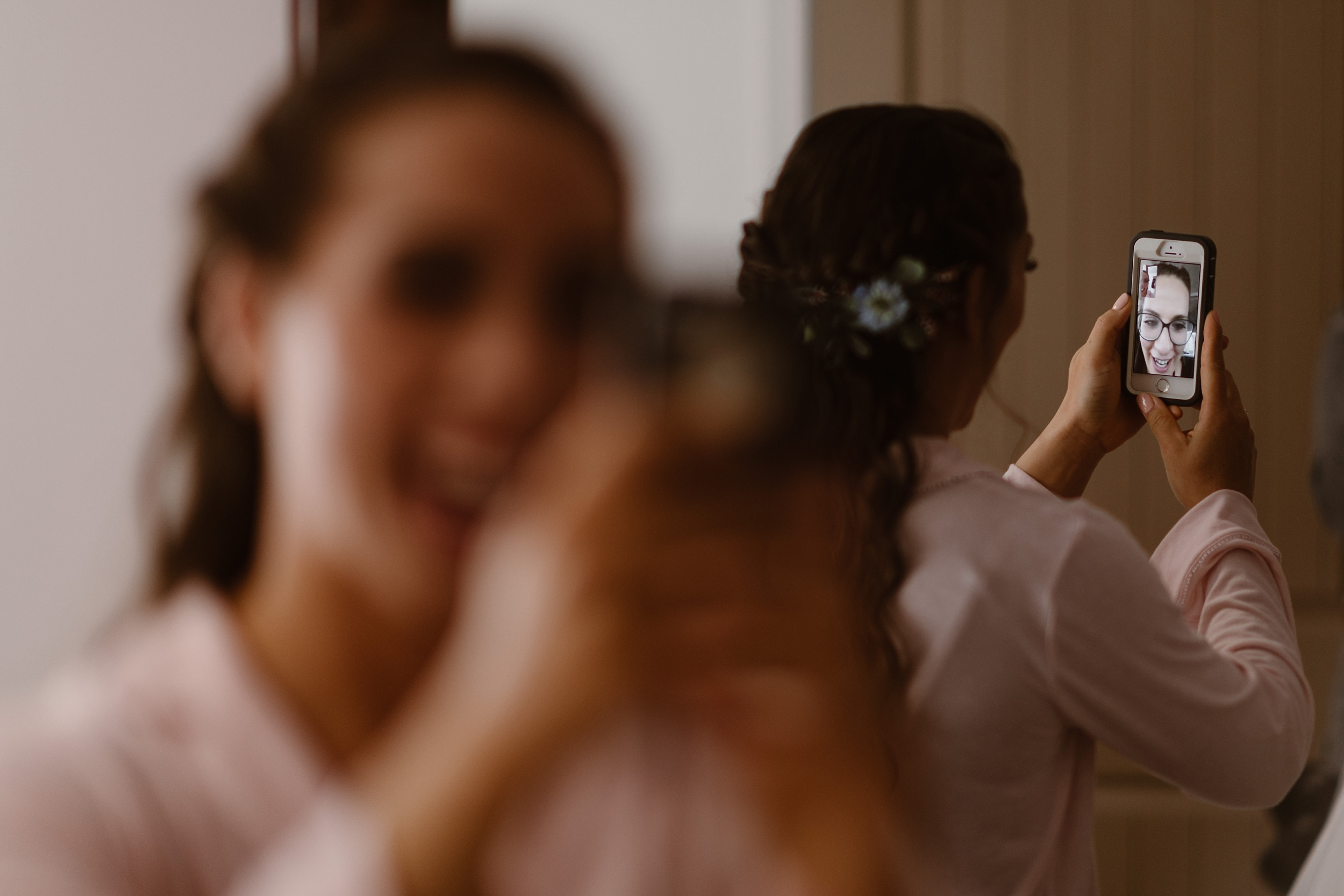 In this image, the bride factimes a loved one in the mirror while she's getting ready for her destination elopement in Alaska. In this image taken by elopement photographer Adventure Instead, the brides face is blurred, but her loved one and the back of her hair are in focus
