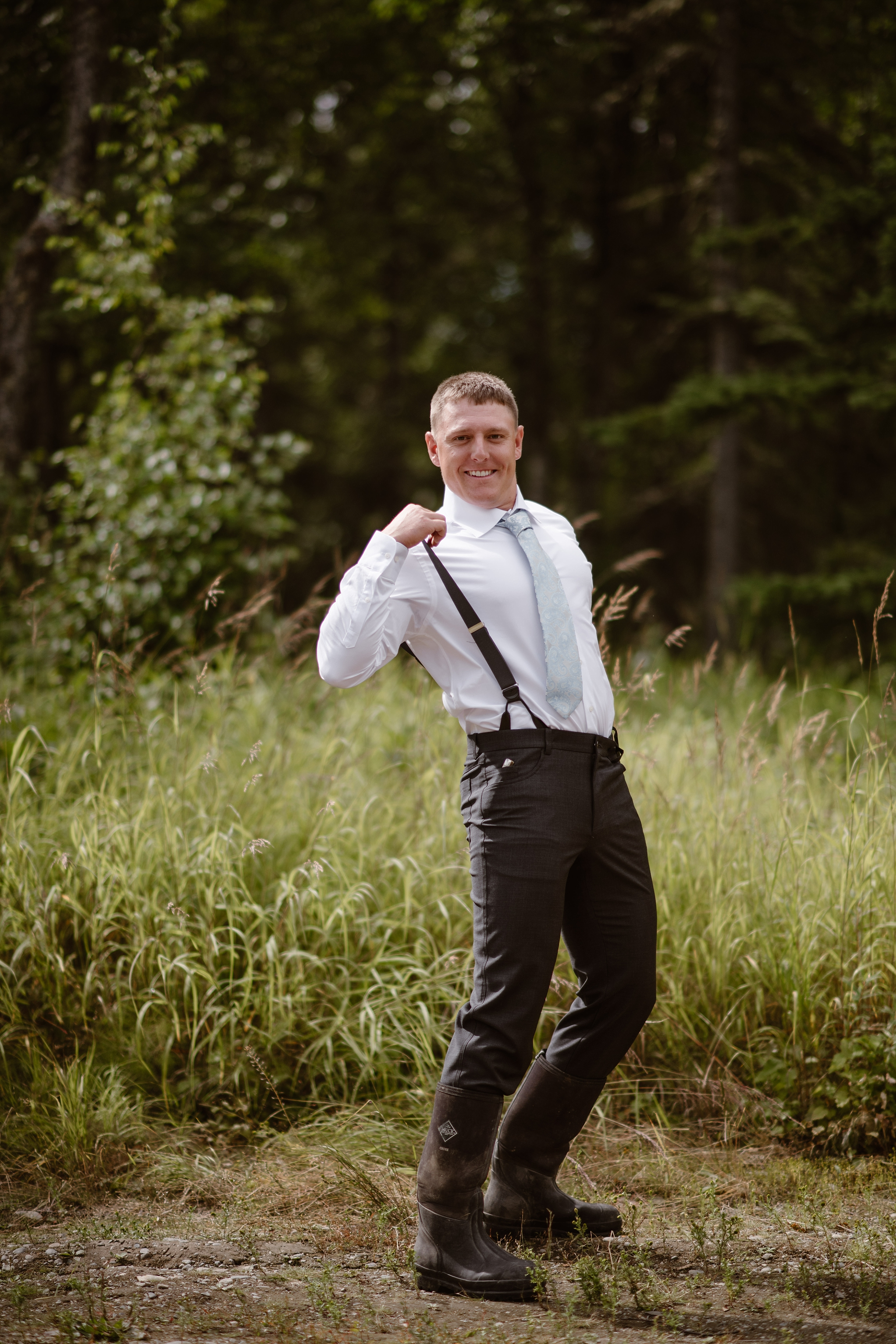 The groom, outfitted in his dress pants, hiking boots, and tie while sporting a goofy face in the lush, green yard of the Alaskan Airbnb. He's pulling on his suspenders in this image captured by Alaska wedding photographers Adventure Instead.