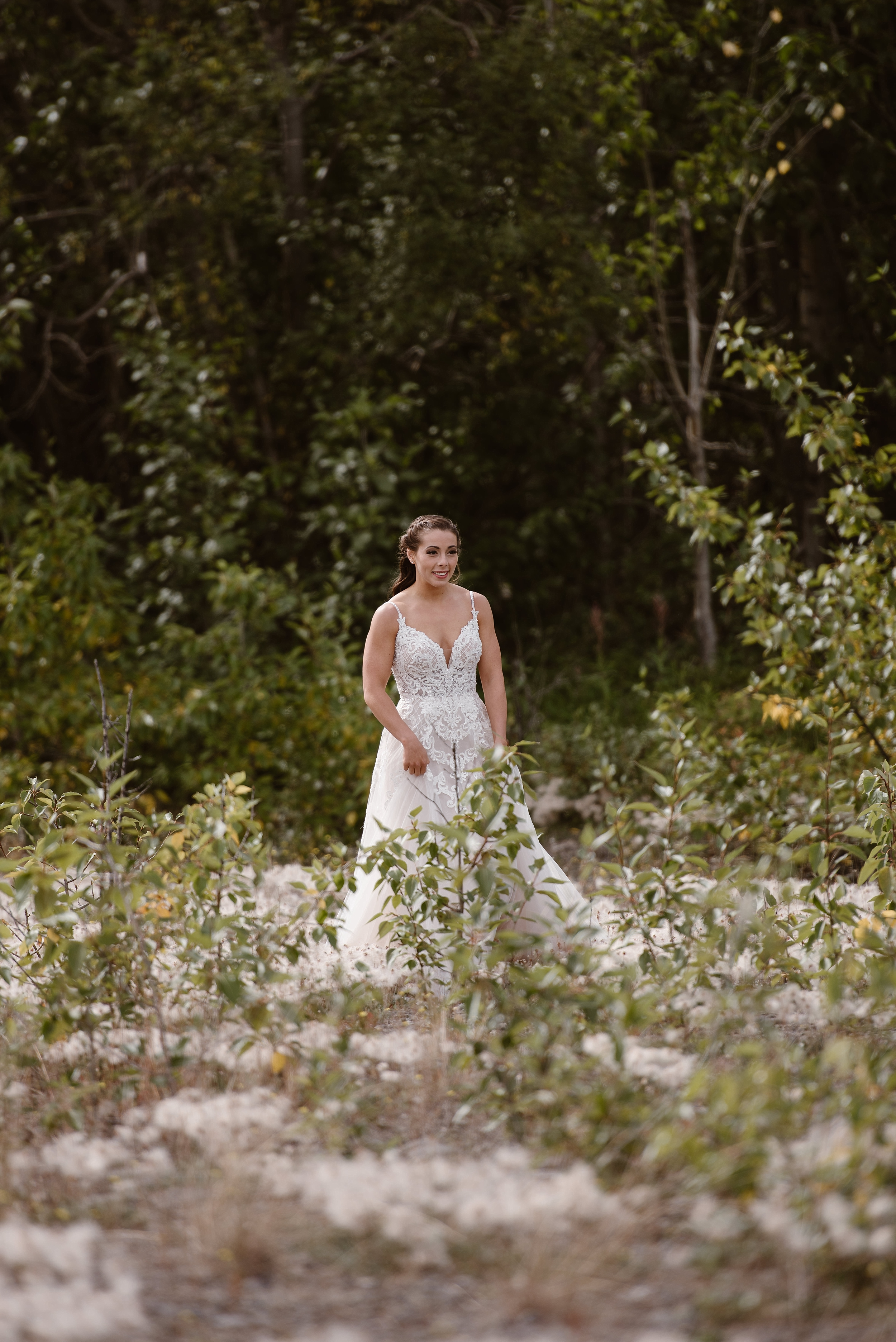 Among lush plants, ferns, and flowers, the bride looks into the distance. Outfitted in her wedding dress in this elopement photo, captured by alaska wedding photographer Adventure Instead, the bride stands out beautifully in white among the green plants surrounding her.