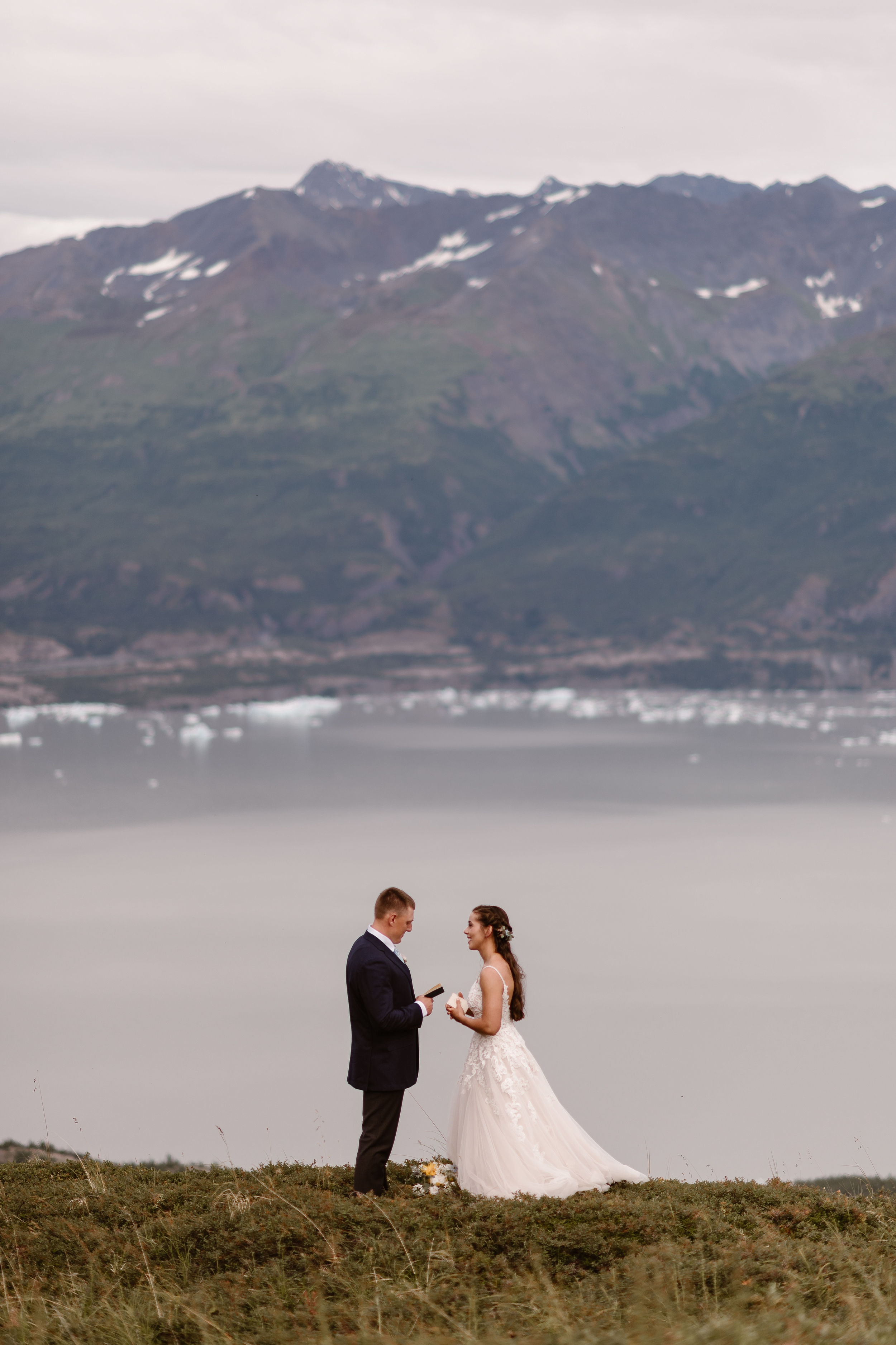 Jordyn and Connor, the bride and the groom, stand in front of a glacial lake with snowy and simultaneously green mountains in the background. The two hold their vow books in their hands as they stare at each other in this elopement ceremony.