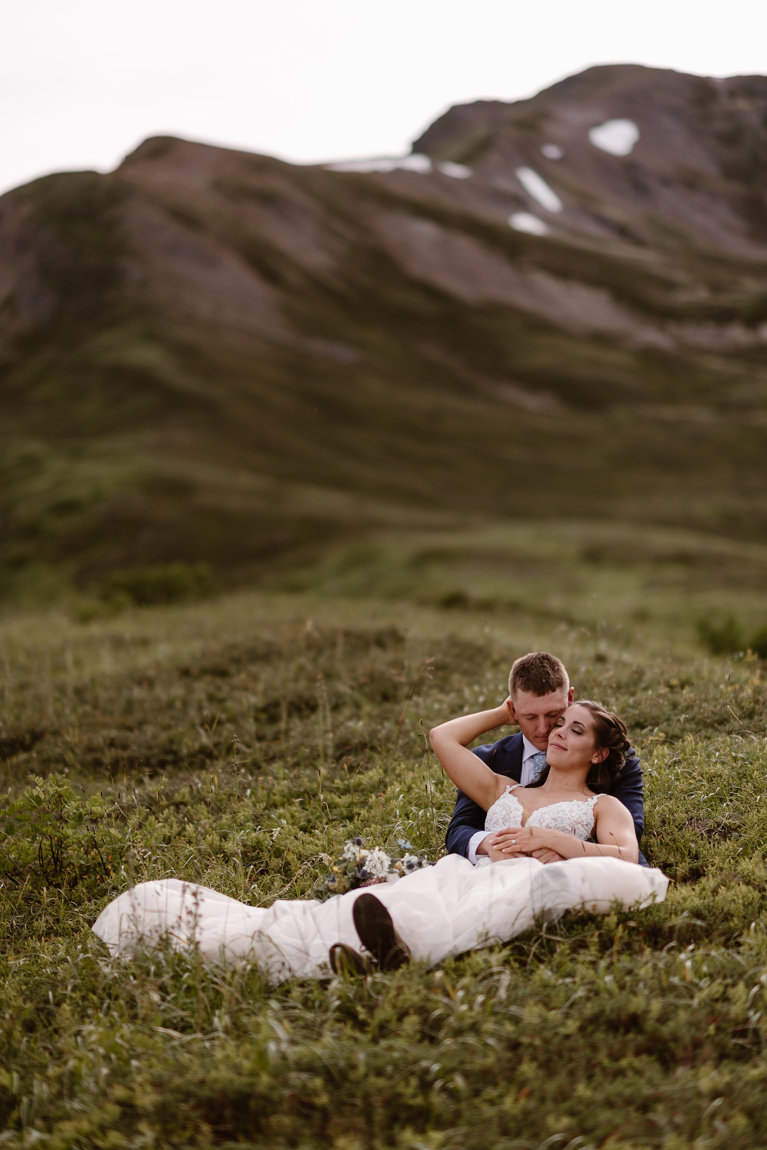 The bride and groom lay in the grass on the green, lush mountain side in Alaska. Jordyn reclines back into Connor's arms, gently reaching back to touch his head. Snowy mountain tops peek out at the top of this elopement photo captured by Alaska wedding photographers Adventure Instead.