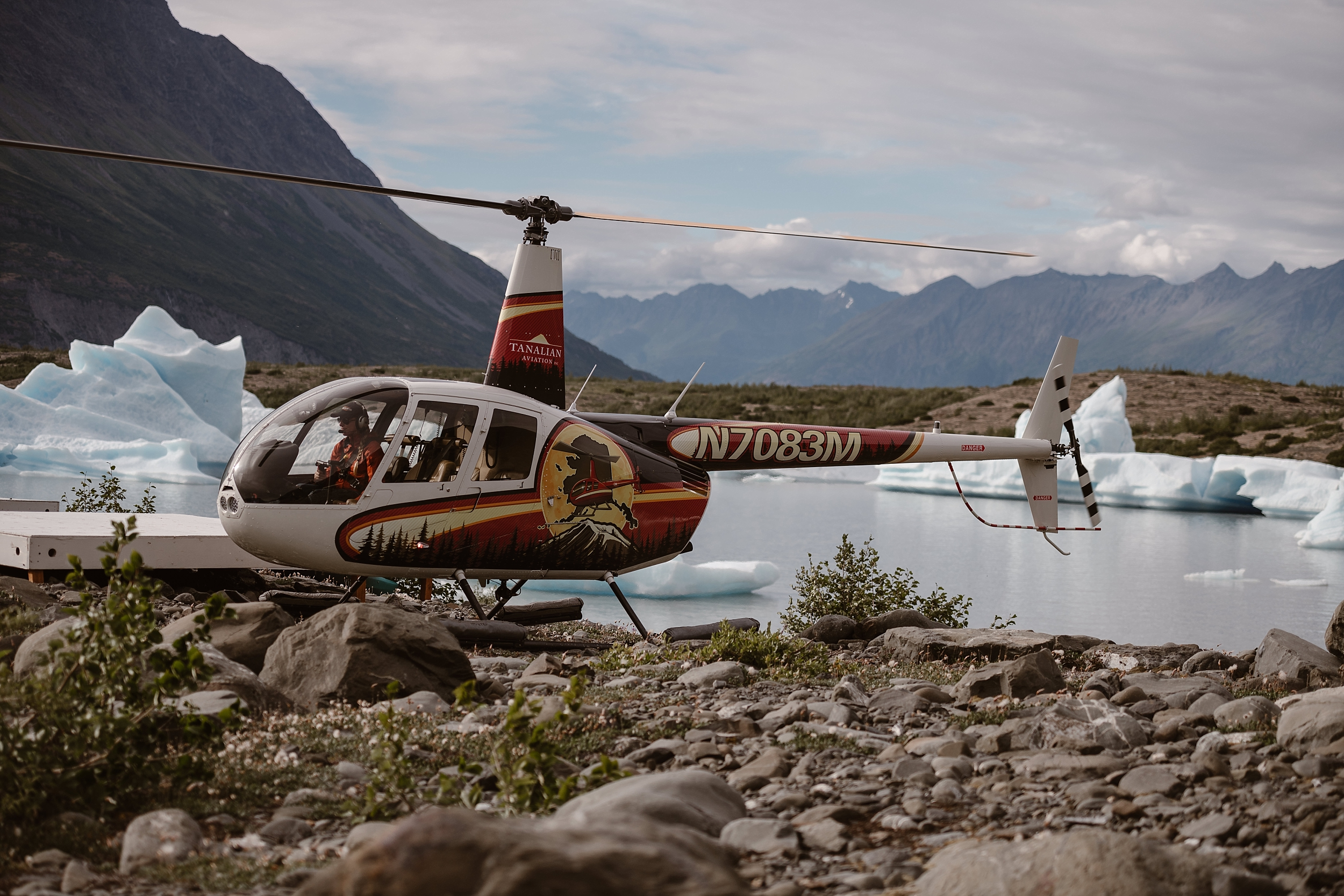 The red, yellow, and white helicopter lands on a rocky beach in front of a glacial lake that has huge chunks of ice floating in it. In the background, giant mountain peaks jut toward the sky.