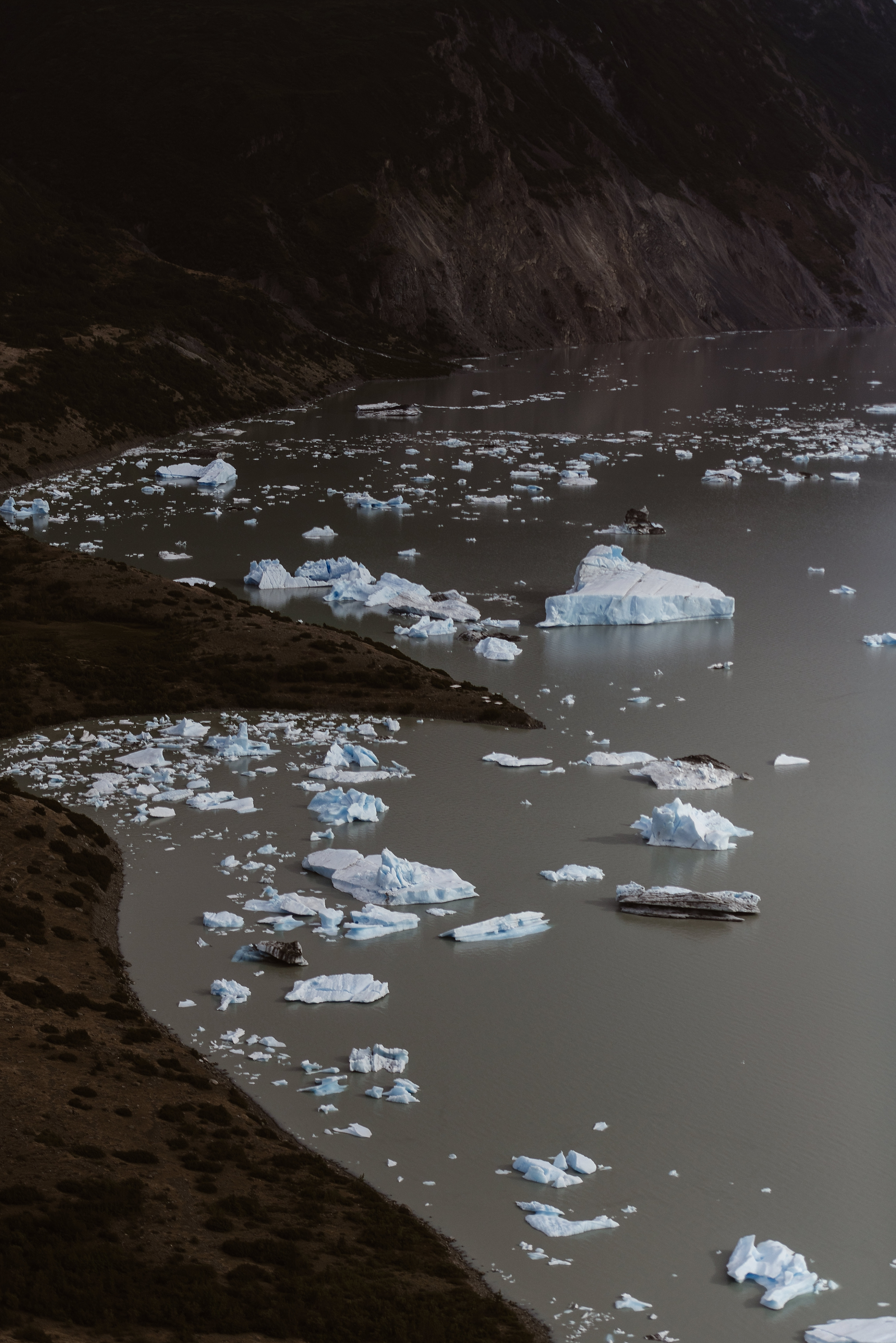 This image, captured by Adventure Instead, an Alaska wedding photographer, shows a birds-eye-view of a glacial lake with large chunks of ices floating within the lake. These features are all things that Jordyn and Connor wanted to see as part of their Alaska helicopter elopement.