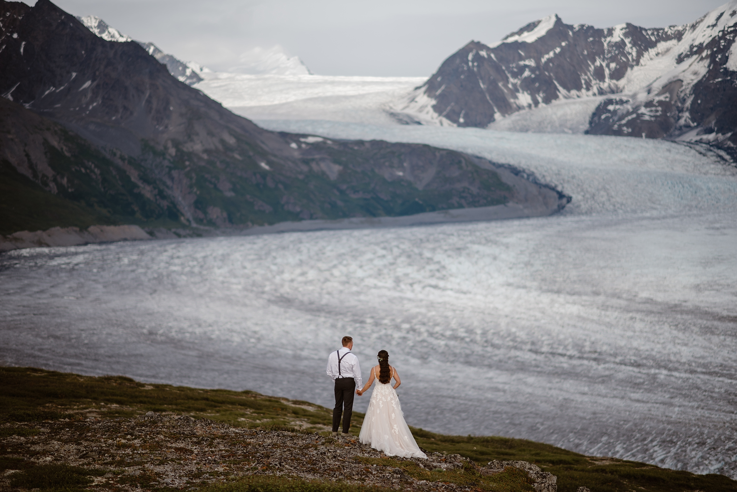 Jordyn and Connor, the bride and groom, gaze off into the distance while they stand, with their backs to the camera, on a green, rocky mountainside. In front of them is a huge glacier, and tons of glaciated peaks covered in ice and snow. These are features that Jordyn and Connor both wanted for their elopement photos and as a big part of their destination elopement.