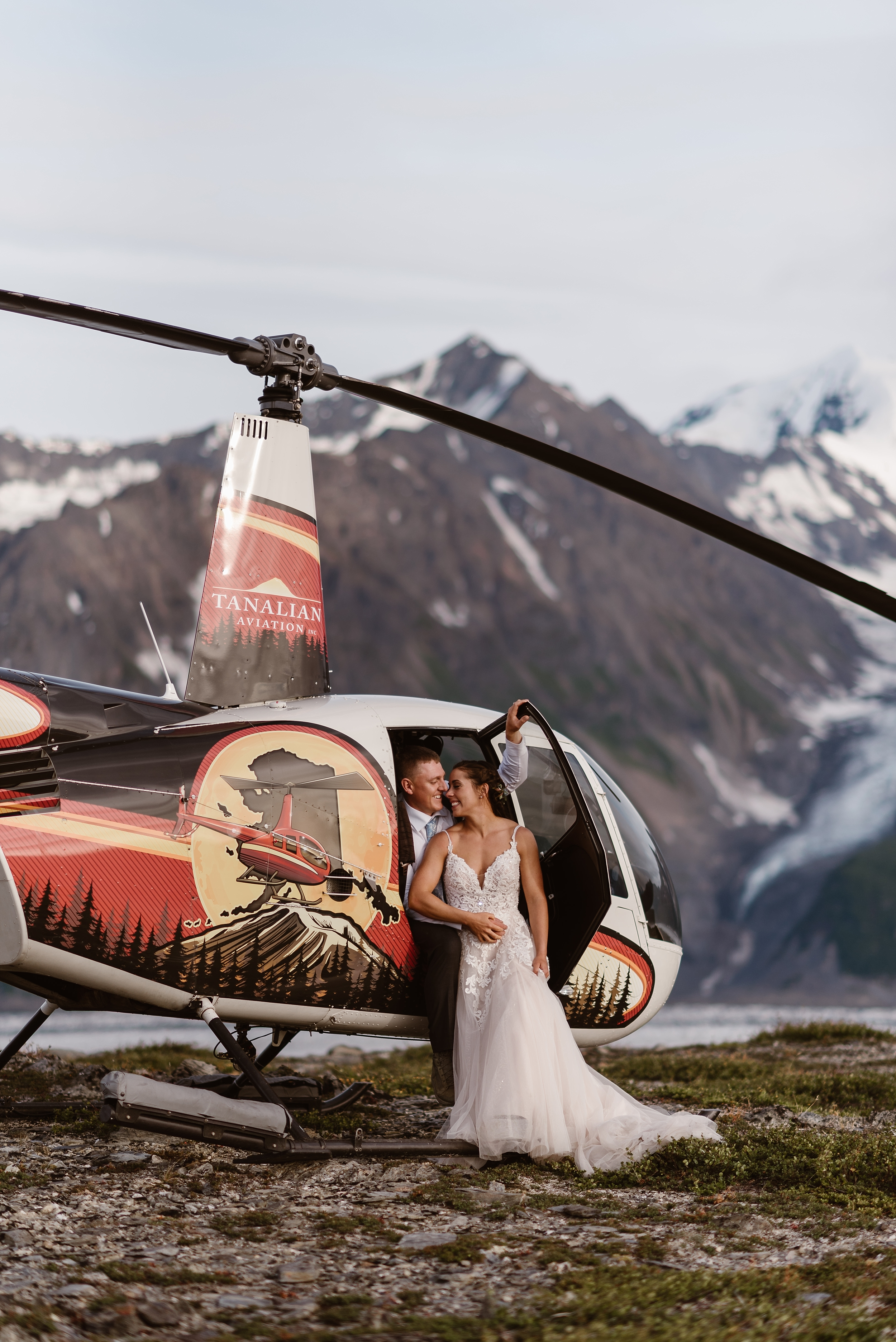 Jordyn and Connor sit halfway inside the helicopter as the nuzzle and closely embrace. Jordyn, sitting on Connor's lap, leans in close to Connor as he holds his hand on the helicopter door. The helicopter is parked on a rocky, green mountainside in front of an enormous mountain with a glacial peak in these elopement photos captured by Adventure Instead, a wedding photographer.