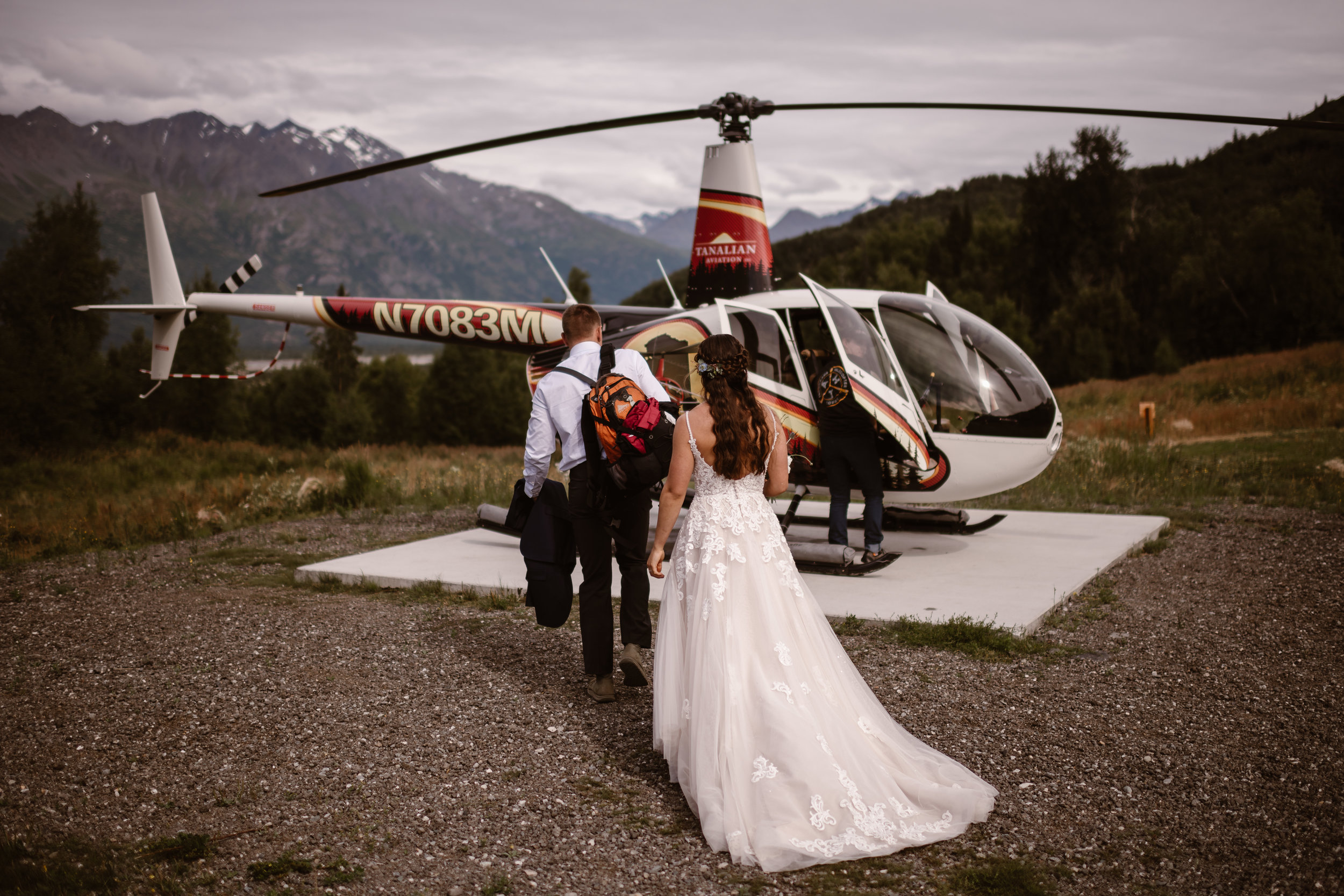 Connor leads the way toward the helicopter as Jordyn follows along close behind. In this elopement picture taken by Adventure Instead, Alaska wedding photographers, the two are about to climb into the red,black, and white helicopter that will take them on their helicopter elopement.