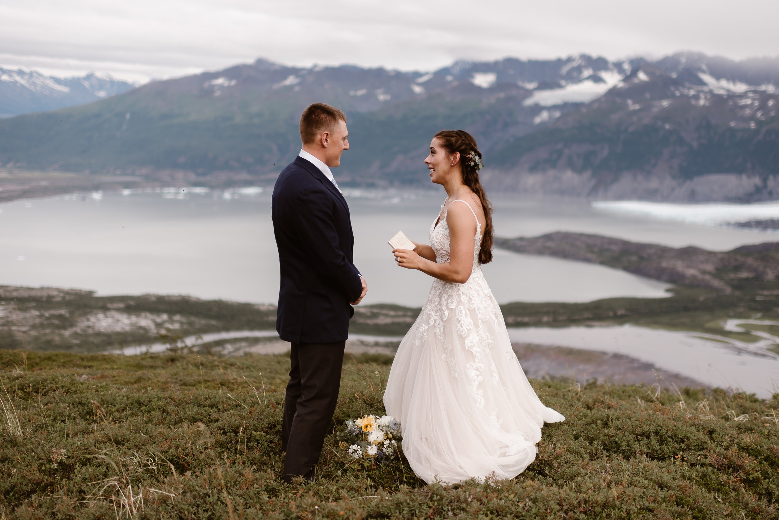 Standing in front of a glacial lake, wild Alaskan mountains, and in a field of green grass, Jordyn reads her vows to her soon-to-be-husband Connor. Connor listens intently in this elopement picture captured by Adventure Instead, Alaska elopement photographers.