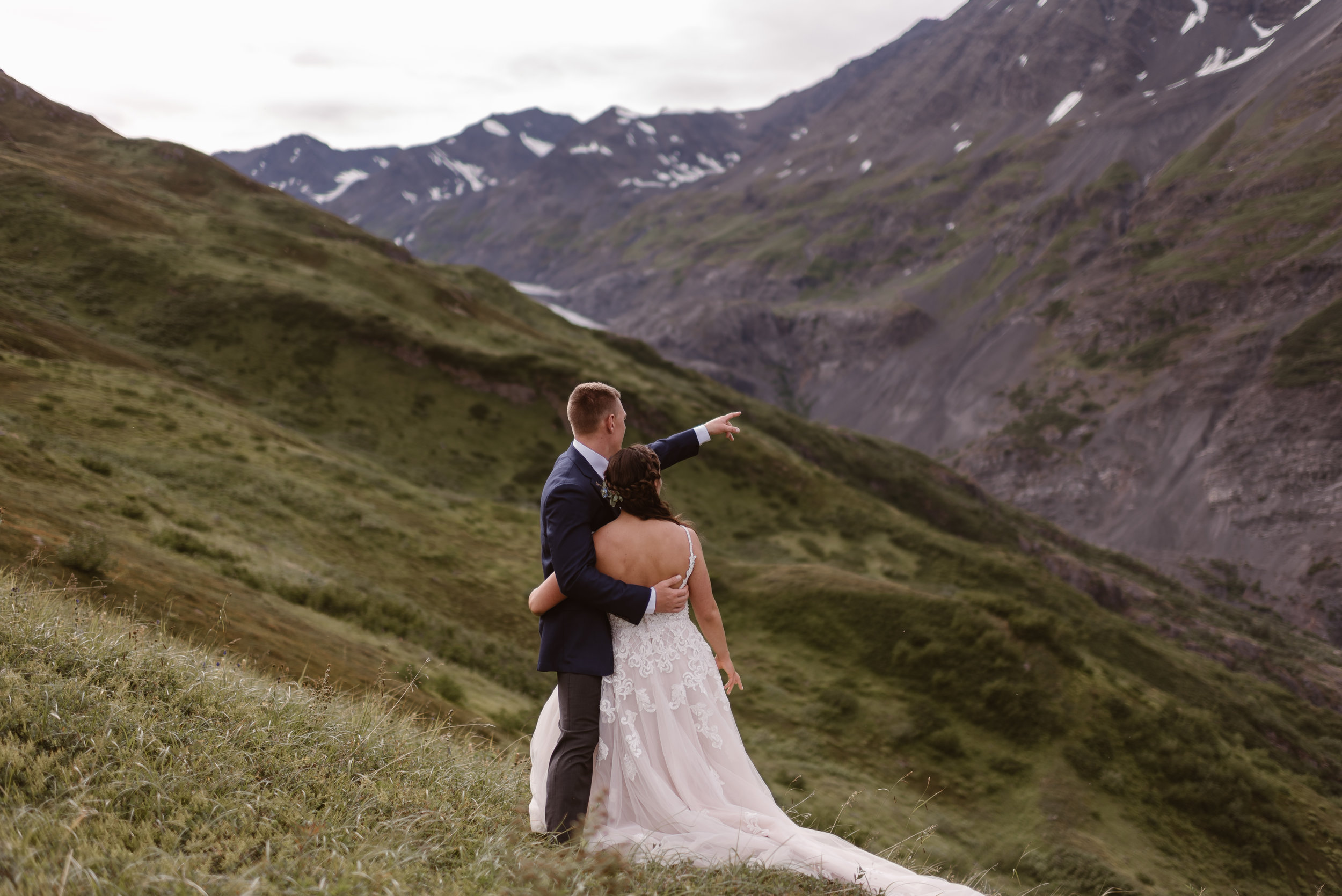 Jordyn and Connor embrace with their backs to the camera in these elopement pictures captured by Adventure Instead, Alaska wedding photographers. Connor points off into the distance beyond the rocky, granite peaks in front of them as they stand on a green, lush mountainside.