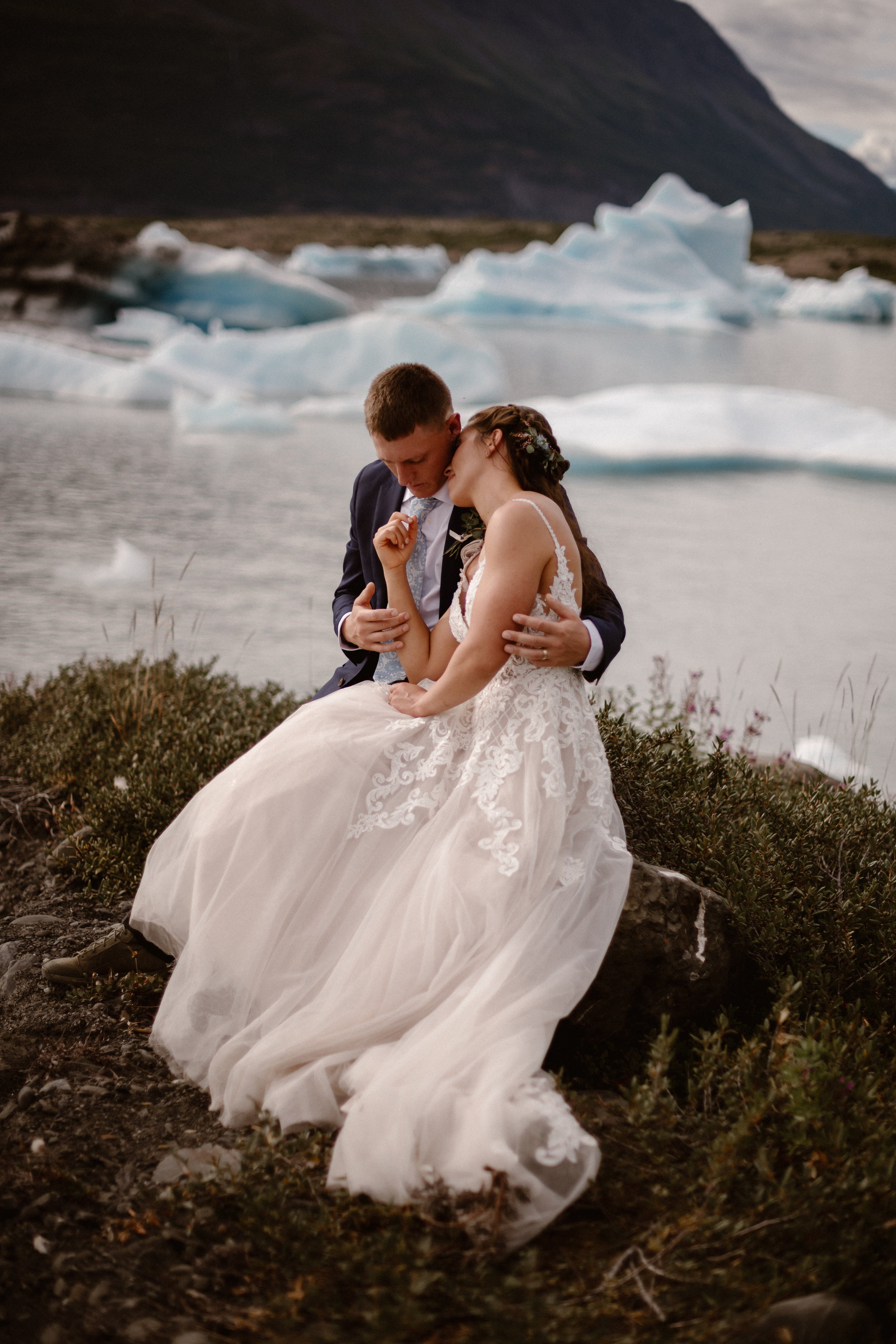 Jordyn and Connor, the bride and groom, cozy up to each other by the side of the glacial lake in these elopement pictures. This Alaska helicopter elopement story was captured by Adventure Instead, an elopement wedding photographer.