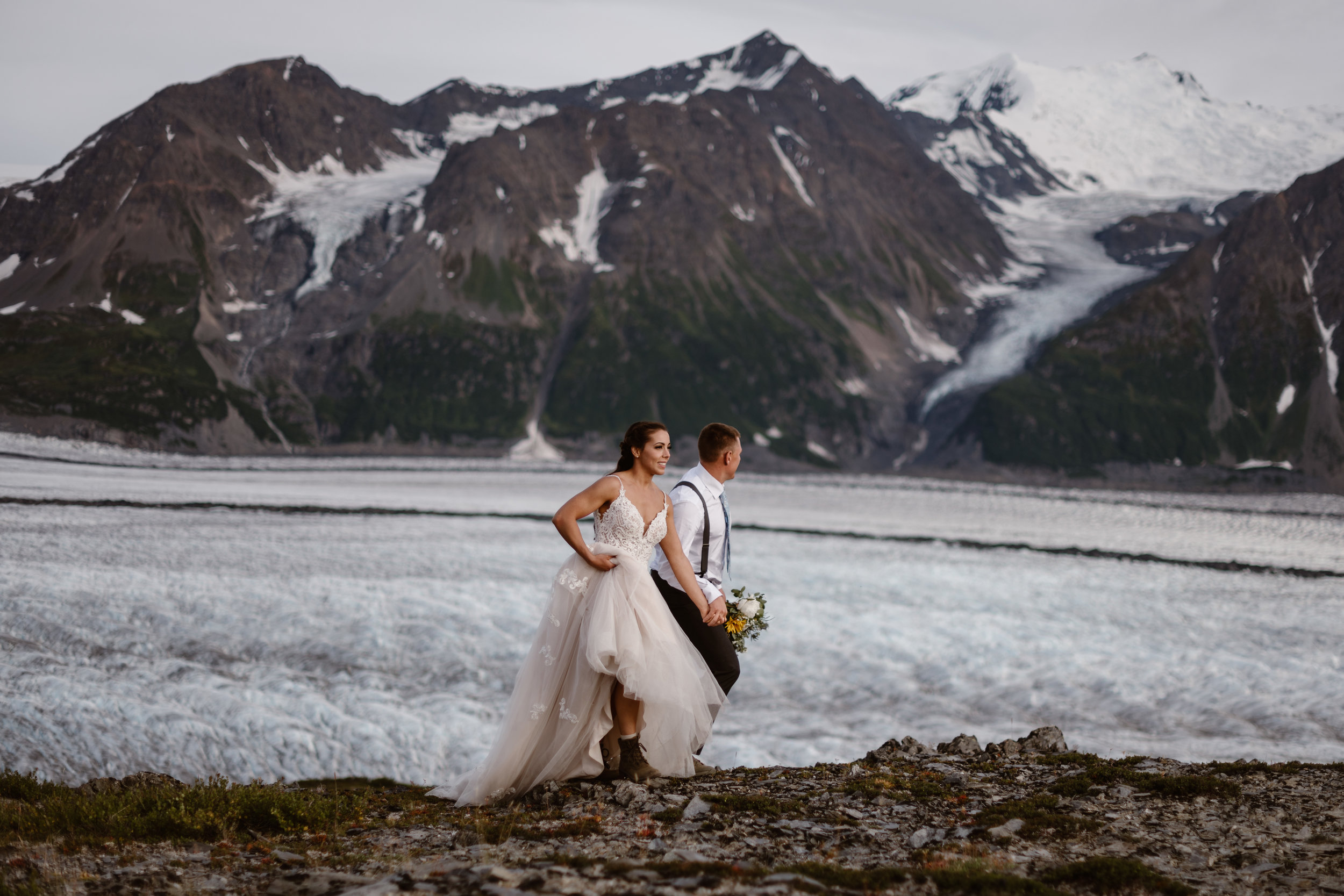 Holding hands, Jordyn and Connor walk along the side of mountain with a glacial lake and mountain peaks standing dramatically in the background. Jordyn hikes up her dress , showing off her hiking boots, and Connor walks next to her holding a bouquet of flowers. This elopement picture was captured by Alaska wedding photographer Adventure Instead.