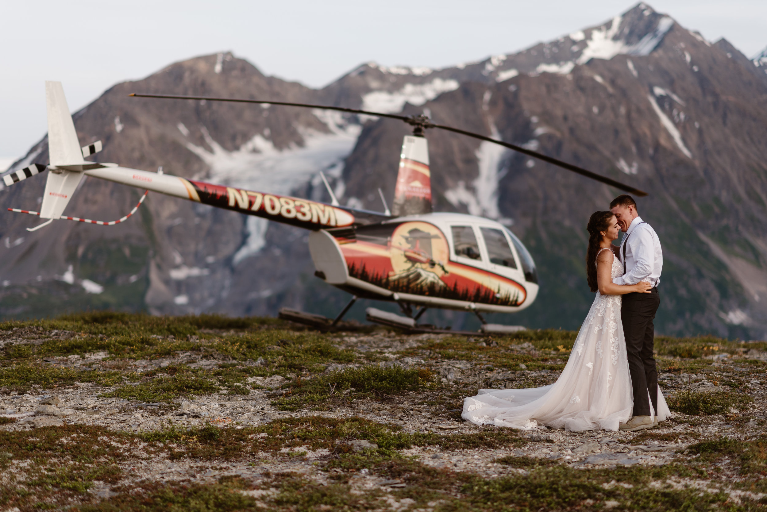 The bride and groom embrace in front of the helicopter on a mountainside, which is parked in front of a granite mountain with an icy peak. These elopement photos were captured by Adventure Instead, Alaska wedding photographers.