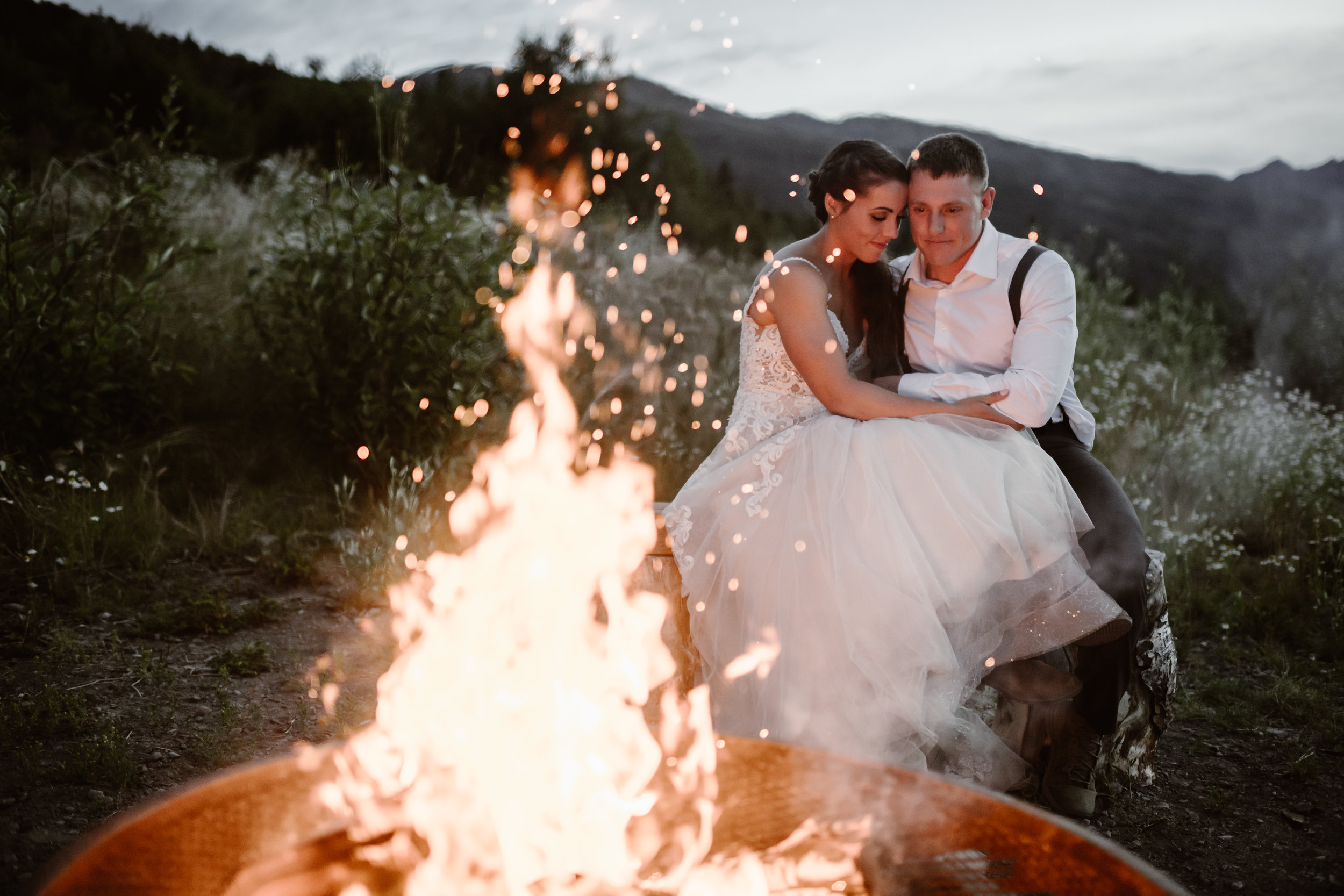 Jordyn and Connor embrace in front of a roaring campfire during Alaska's blue hour. They chose to sit by the fire and have their first dance here as part of their party after eloping. This destination elopement was captured by Adventure Instead, Alaska wedding photographers.