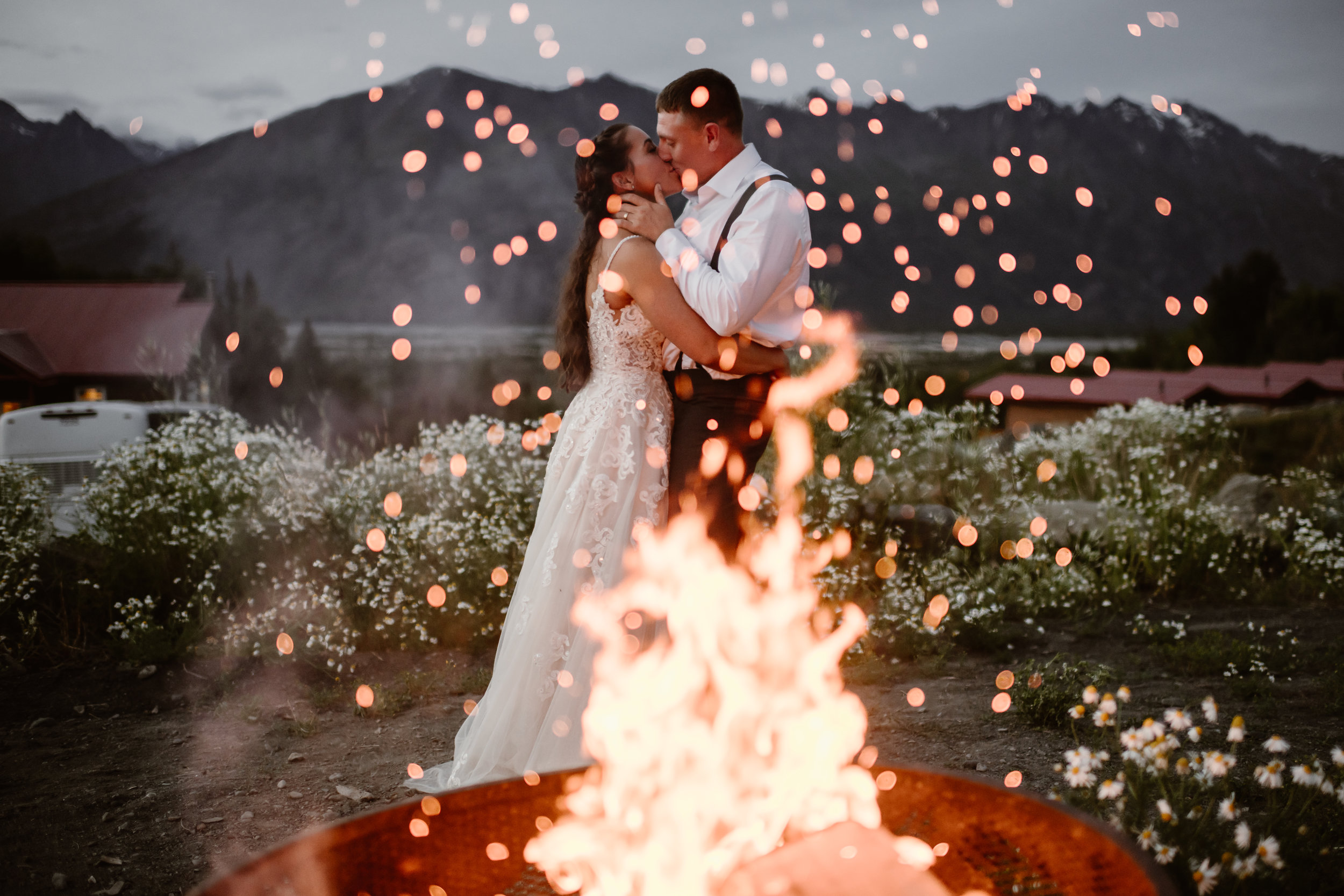 In the midst of a sparking campfire with enormous mountains in the background, Jordyn and Connor kiss at the finale of their first dance and the end of their reception after eloping. Jordyn and Connor's Alaska helicopter elopement story was captured by Adventure Instead, an elopement wedding photographer.