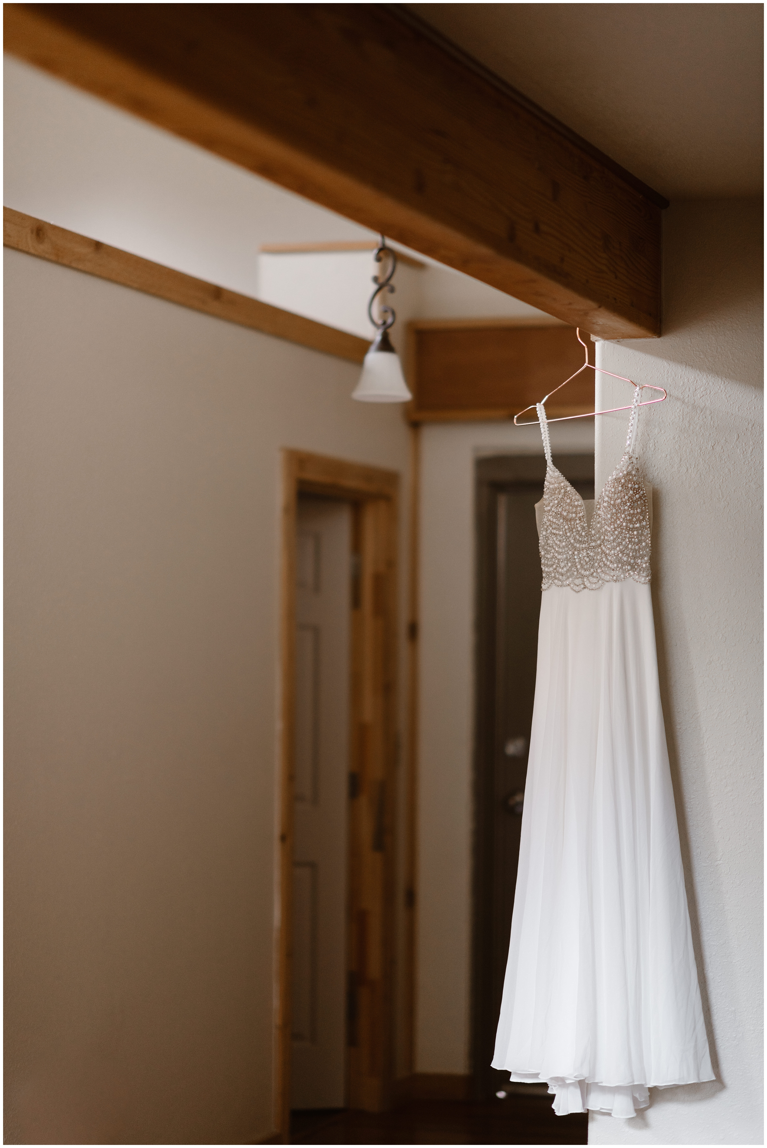 A sleek, white wedding dress hangs from the ceiling in an Ouray, Colorado Airbnb. The dress, white with pearl details on the top of the bodice, hangs from a pink hangar from a wooded rafter. These elopement photos were captured by adventure wedding photographer Adventure Instead.