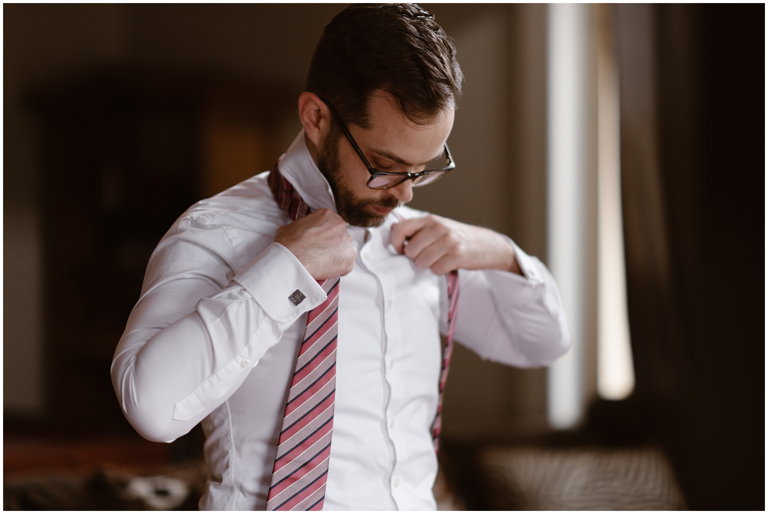 Logan, the groom, gets ready in the Airbnb in Ouray, Colorado that the couple rented as part of their adventure elopement. Logan adjusts a peach and light purple tie around his neck while he finishes up preparing for their 4x4 wedding. This photo was captured by Adventure Instead, an elopement wedding photographer.