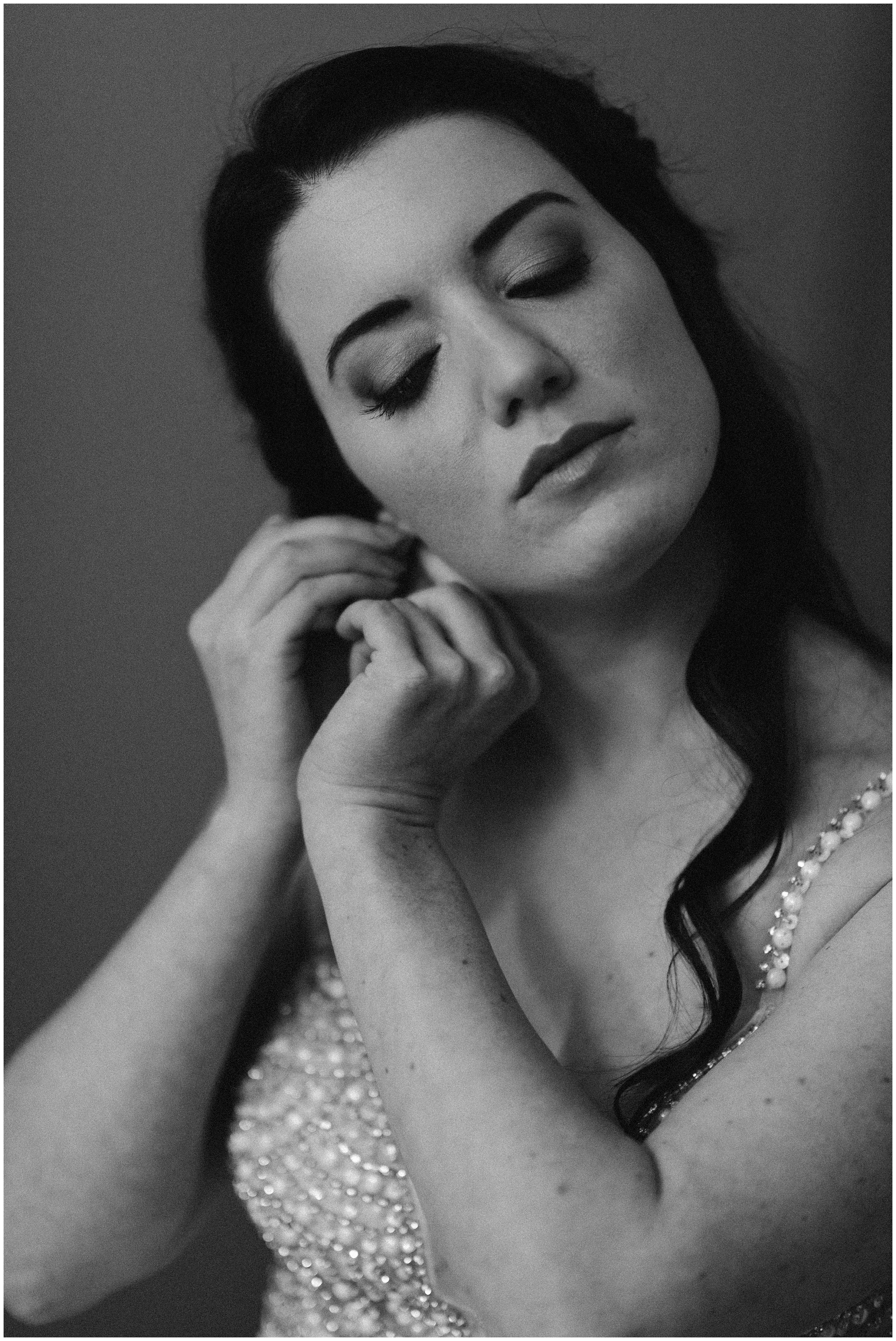 This black and white elopement photo captured by adventure wedding photographer Adventure Instead shows Katie putting on a pearl earring on her right ear. Her dress, beaded with pearl details, glistens in the light.