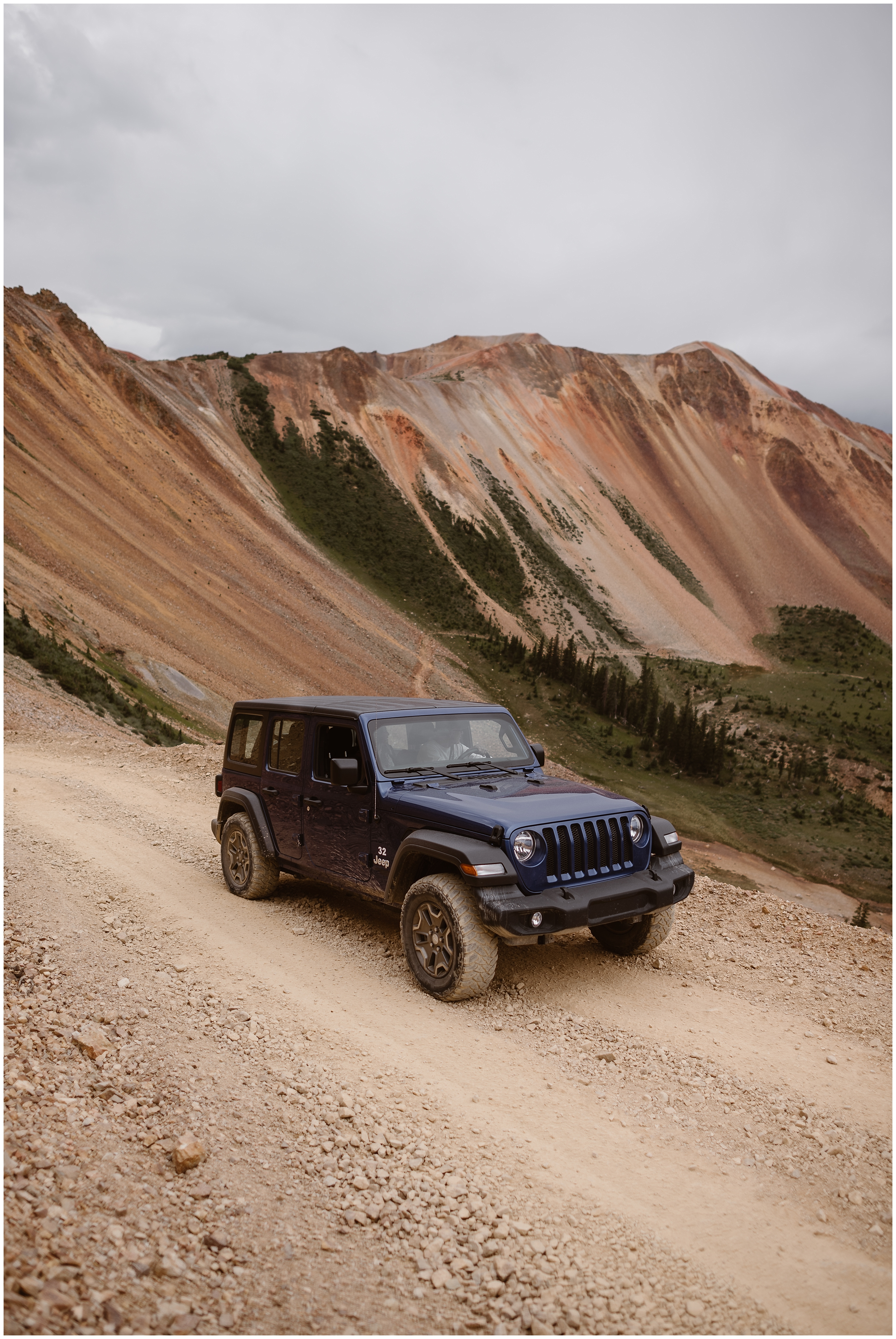 The adventure Jeep wedding car parks along the side of an off road 4x4 path so that Katie and Logan can prepare for their Colorado mountain wedding. The red mountains in the background juxtapose against the navy blue color of the jeep and the green meadows far below them.