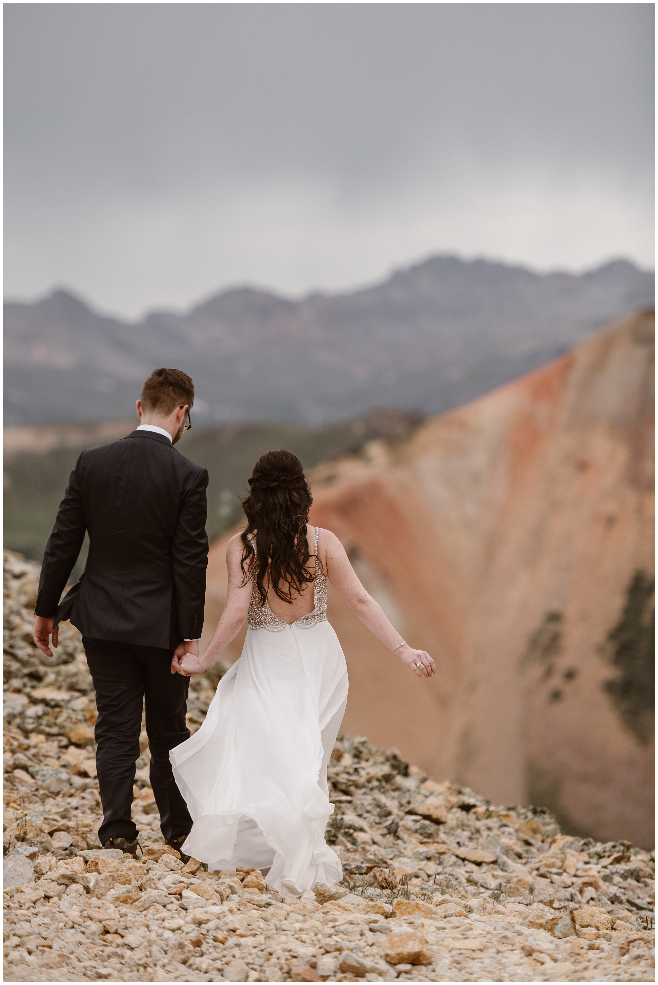 Katie and Logan, the bride and groom, hold hands and walk away from the camera, along the rocky path of the off road 4x4 area. Katie's dress whips around in the wind as they hike up toward a special location, one of their eloping ideas they had for their Colorado elopement.