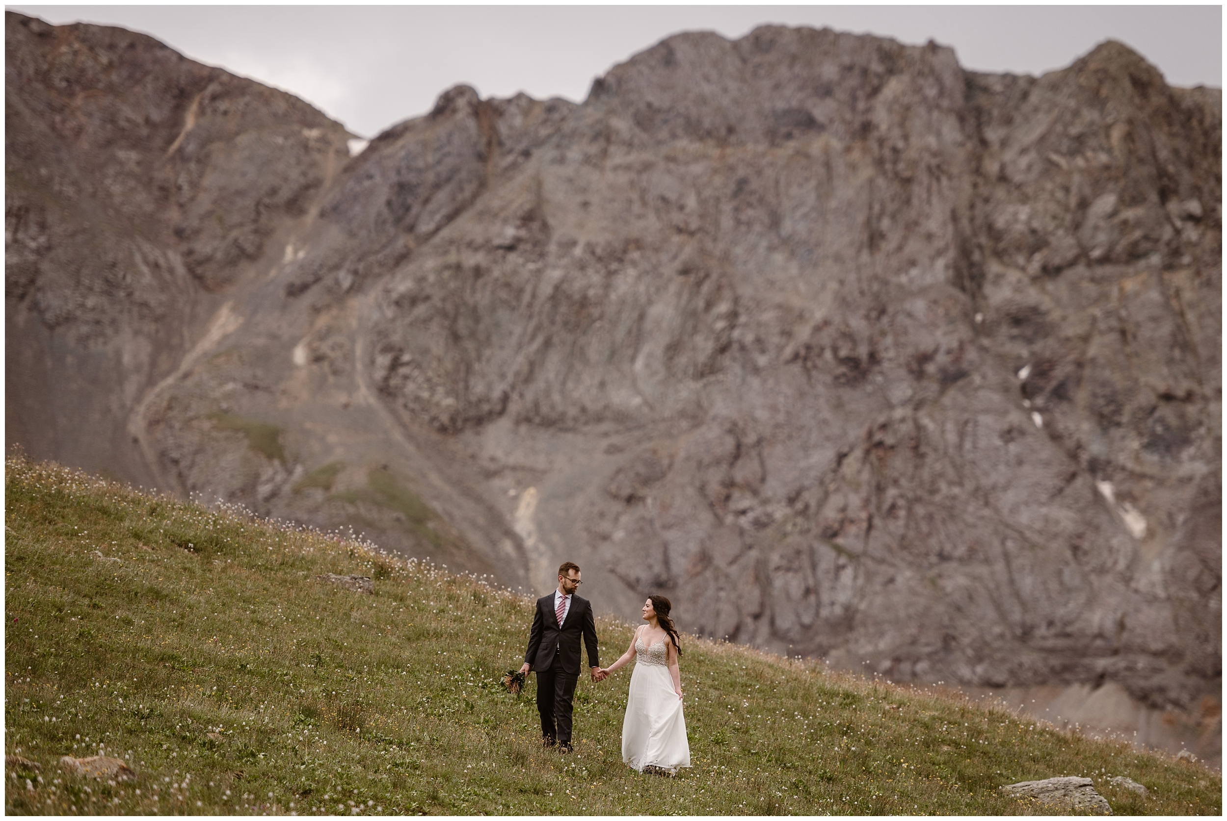 Katie and Logan stand in a green meadow dotted with wildflowers holding hands. Behind them, an enormous granite part of the mountain looms. The two look at each other as they hike to their Colorado mountain wedding location.